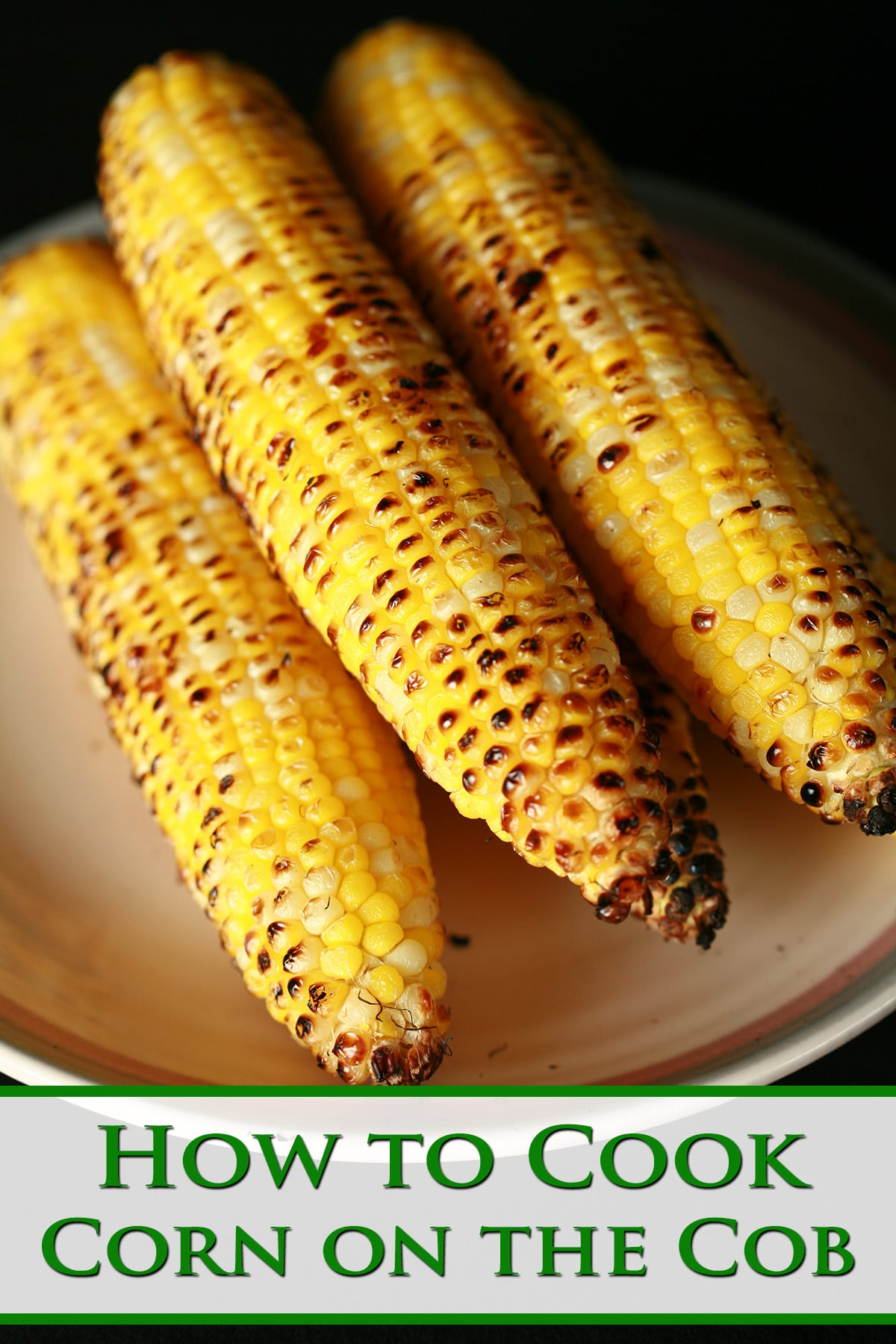 A pile of 5 ears of grilled corn on the cob, on a beige plate. Green text says How to Cook Corn on the Cob.
