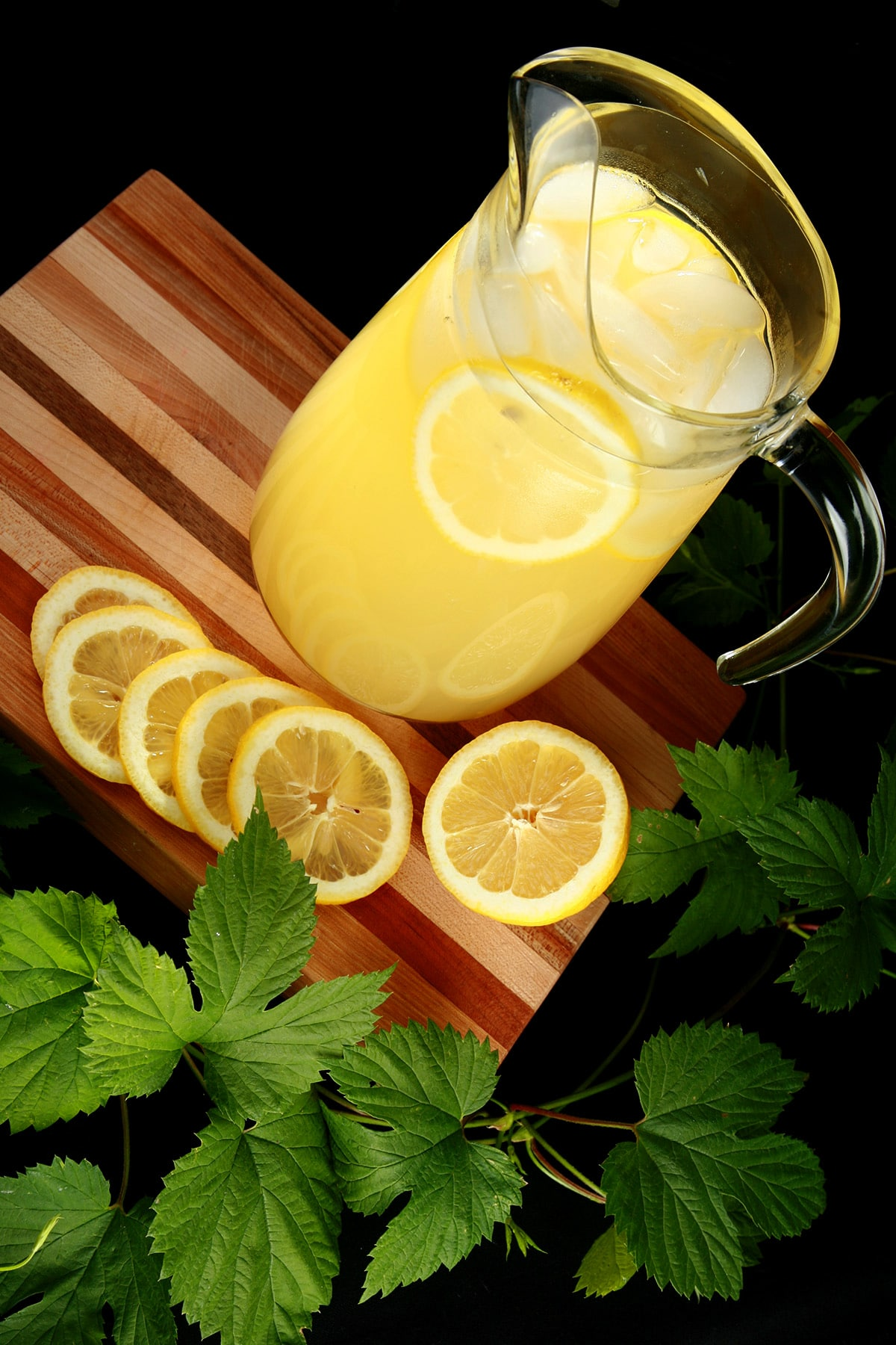 A pitcher of hop lemonade rests on a wooden board, with slices lemons and a hop bine next to it.