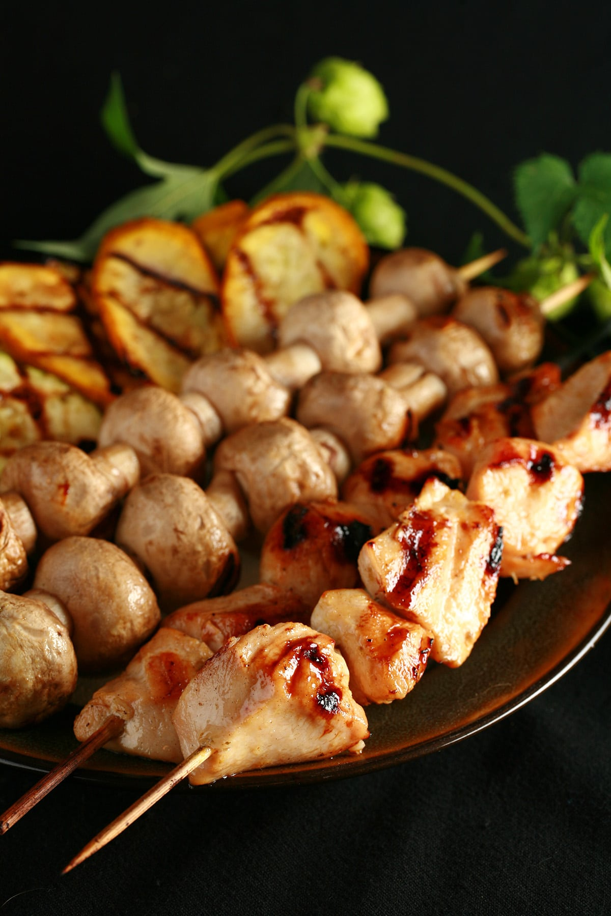 Skewers of hop-marinated grilled chicken, mushrooms, and zucchini are lined up on a brown platter. A hop bine with flowers wraps around the back end of the platter.