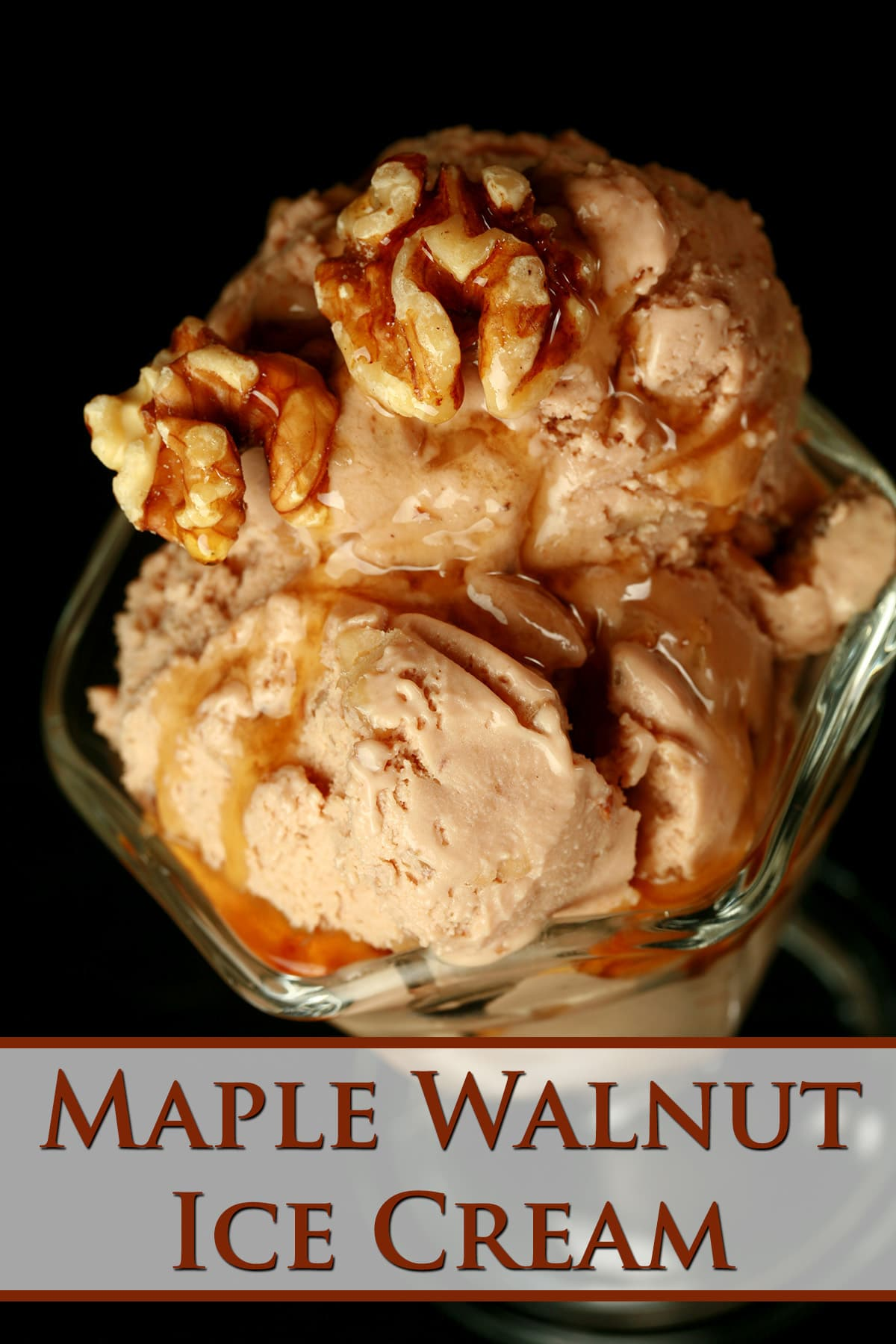 A glass dessert flute has several scoops of homemade maple walnut ice cream stacked in it. It has been drizzled with maple syrup and topped with toasted walnuts.