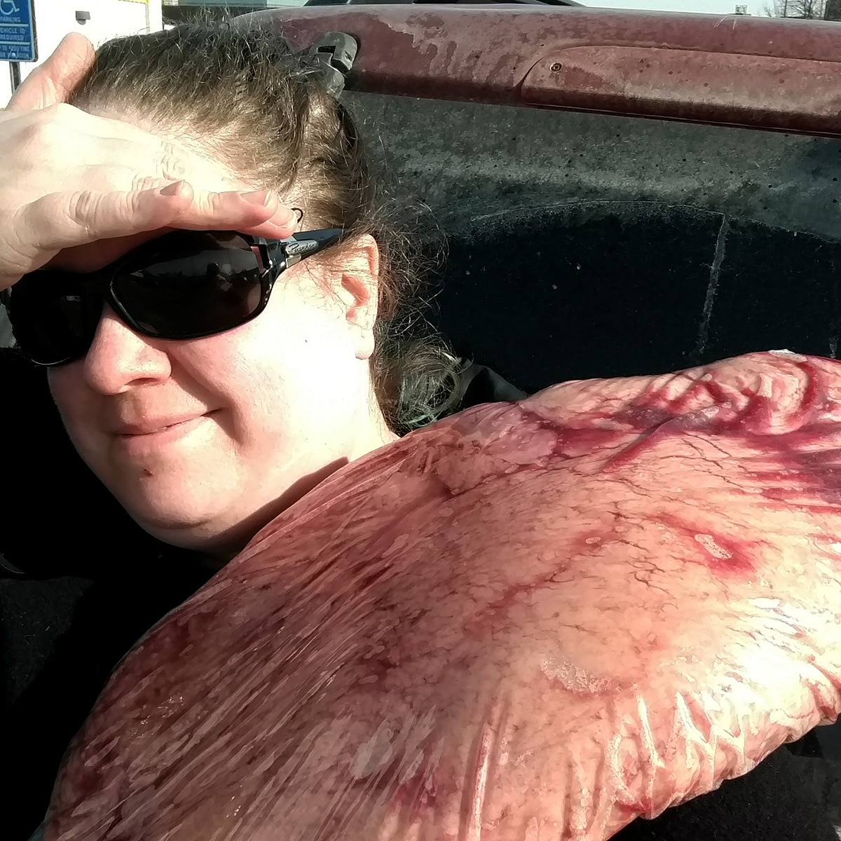 The author, wearing sunglasses, is taking a selfie with a large slab of bagged meat slung over her shoulder.
