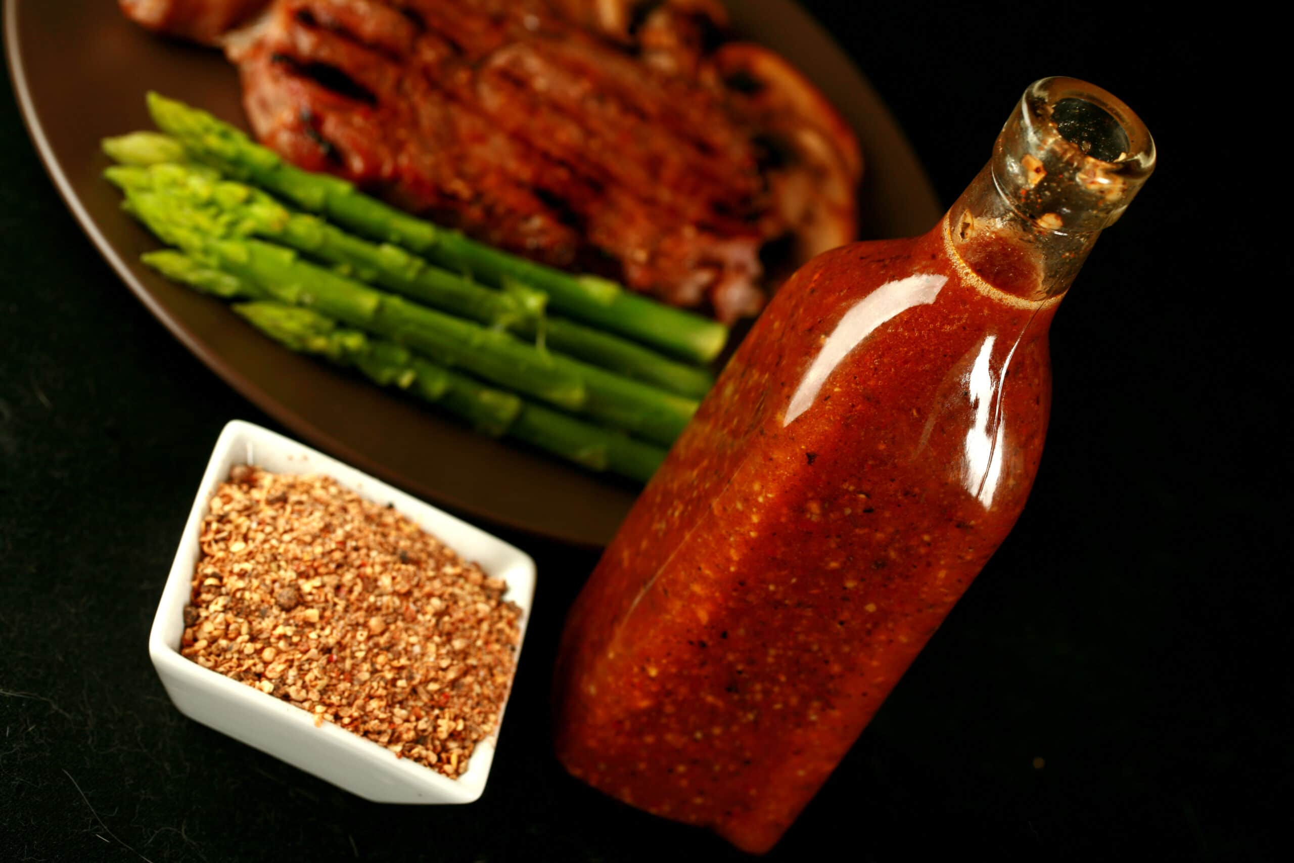 Montreal steak spice in a small square bowl, and marinade in a glass bottle. Behind them, a steak with sauteed mushrooms and asparagus on a plate.
