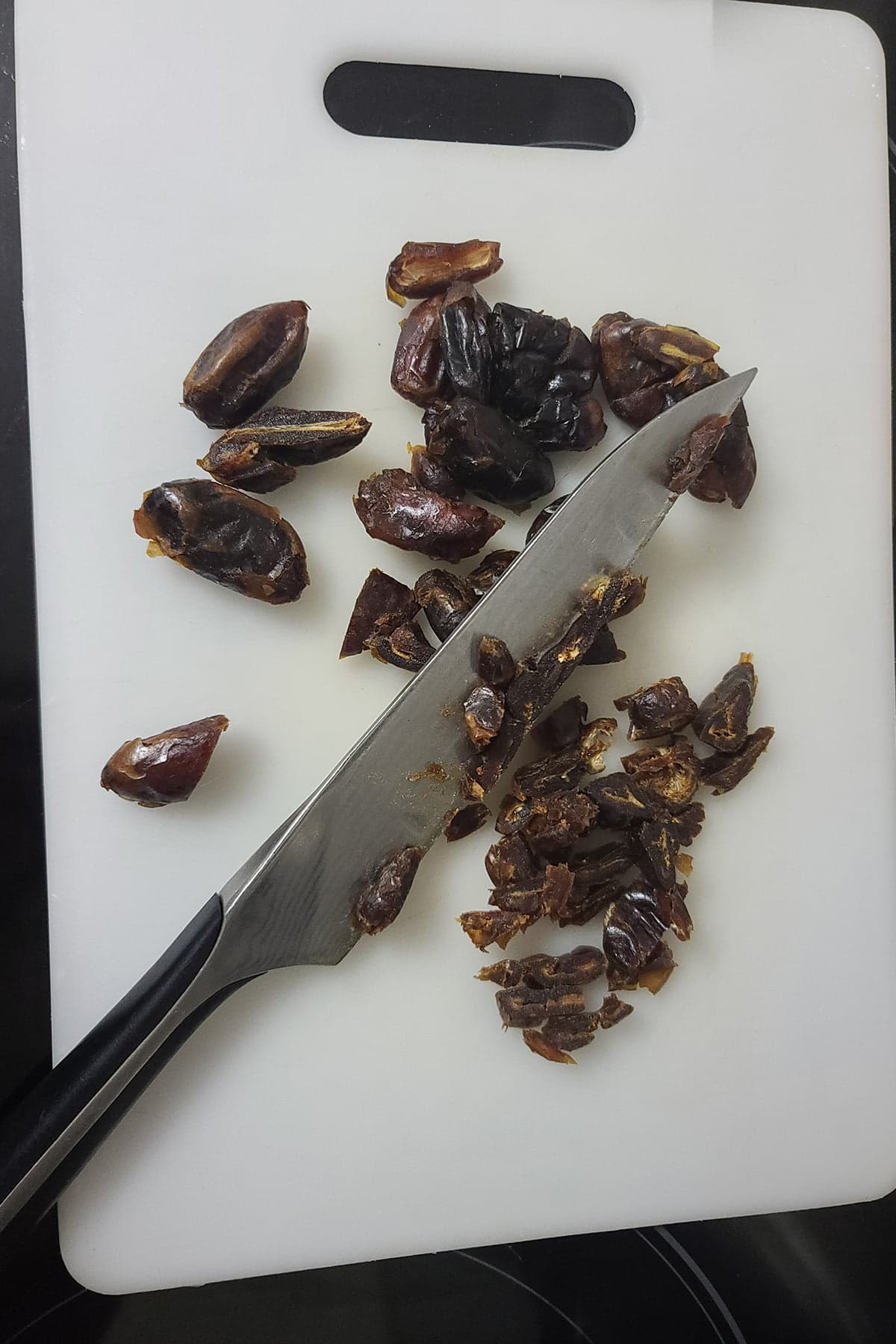 Dried dates on a cutting board, with a knife.