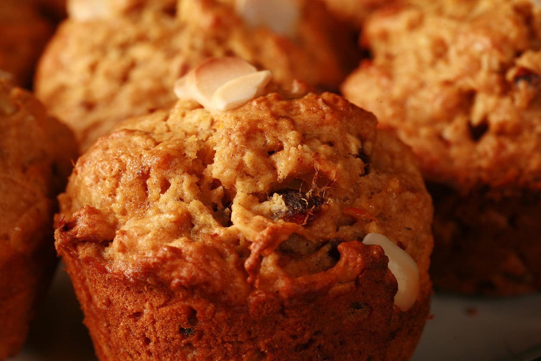 A plate of orange-brown muffins, with slices of almonds and chunks of dates visible throughout.
