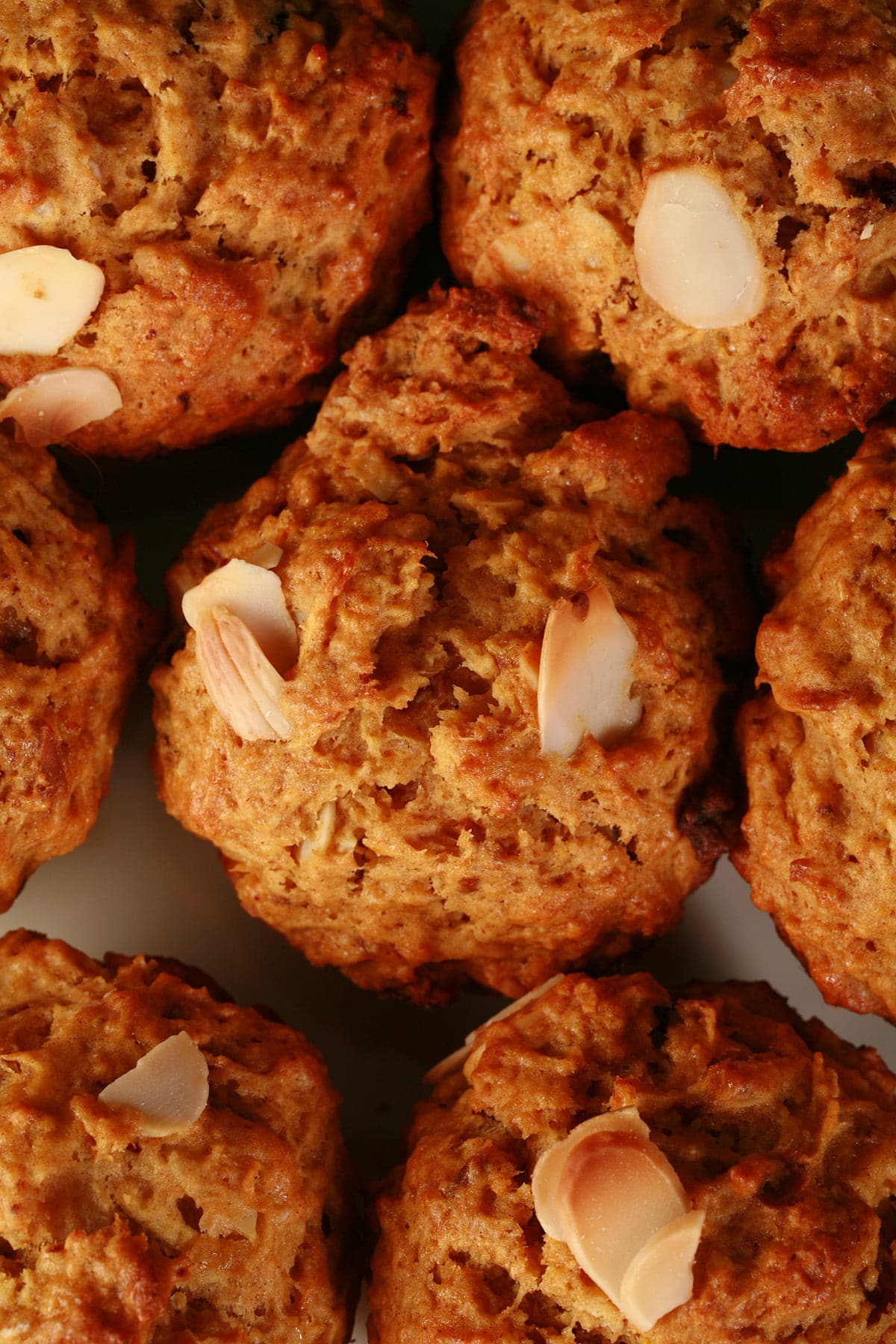 A plate of orange date and almond muffins. They are an orangey brown colour, with slices of almonds and chunks of dates visible throughout.