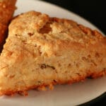 A close up view of Smoked Gouda and Chive scones on a small white plate.