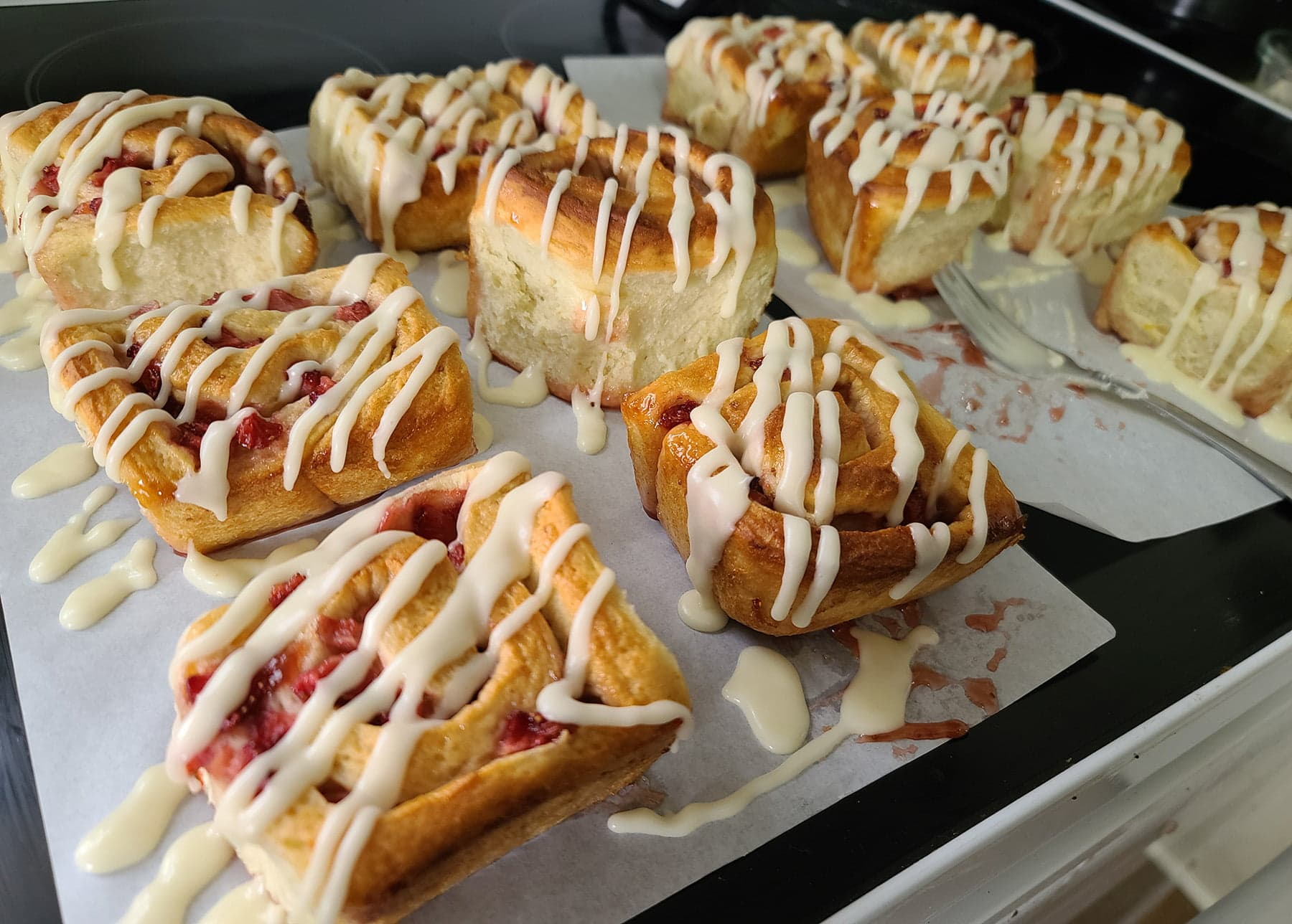 11 strawberry orange rolls are arranged on a sheet of parchment, with a pale orange glaze drizzled across in a zog zag fashion.