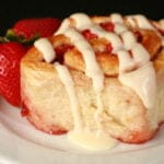 A strawberry orange roll on a white plate, with 2 fresh strawberries next to it.