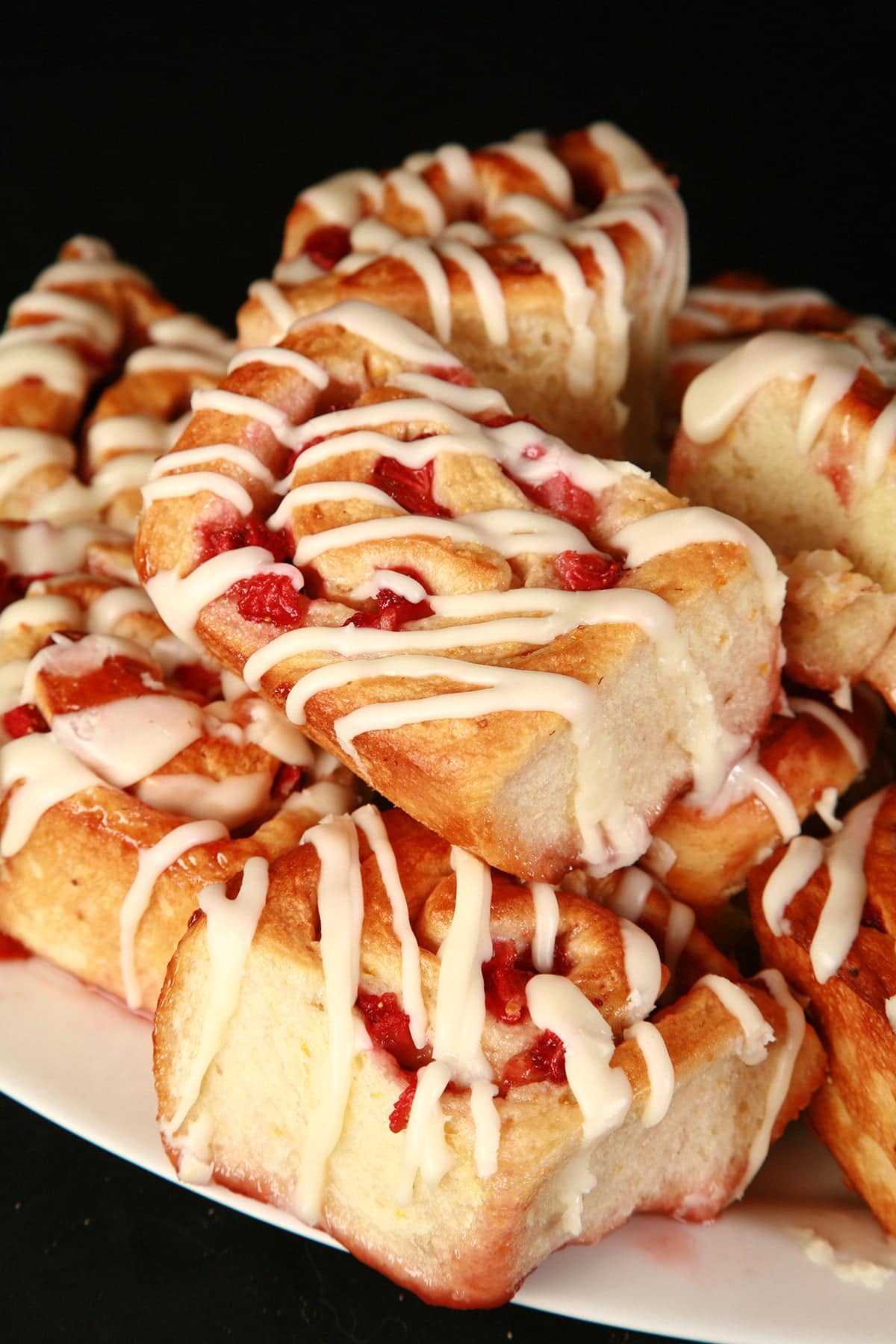 A plate stacked with orange strawberry rolls.