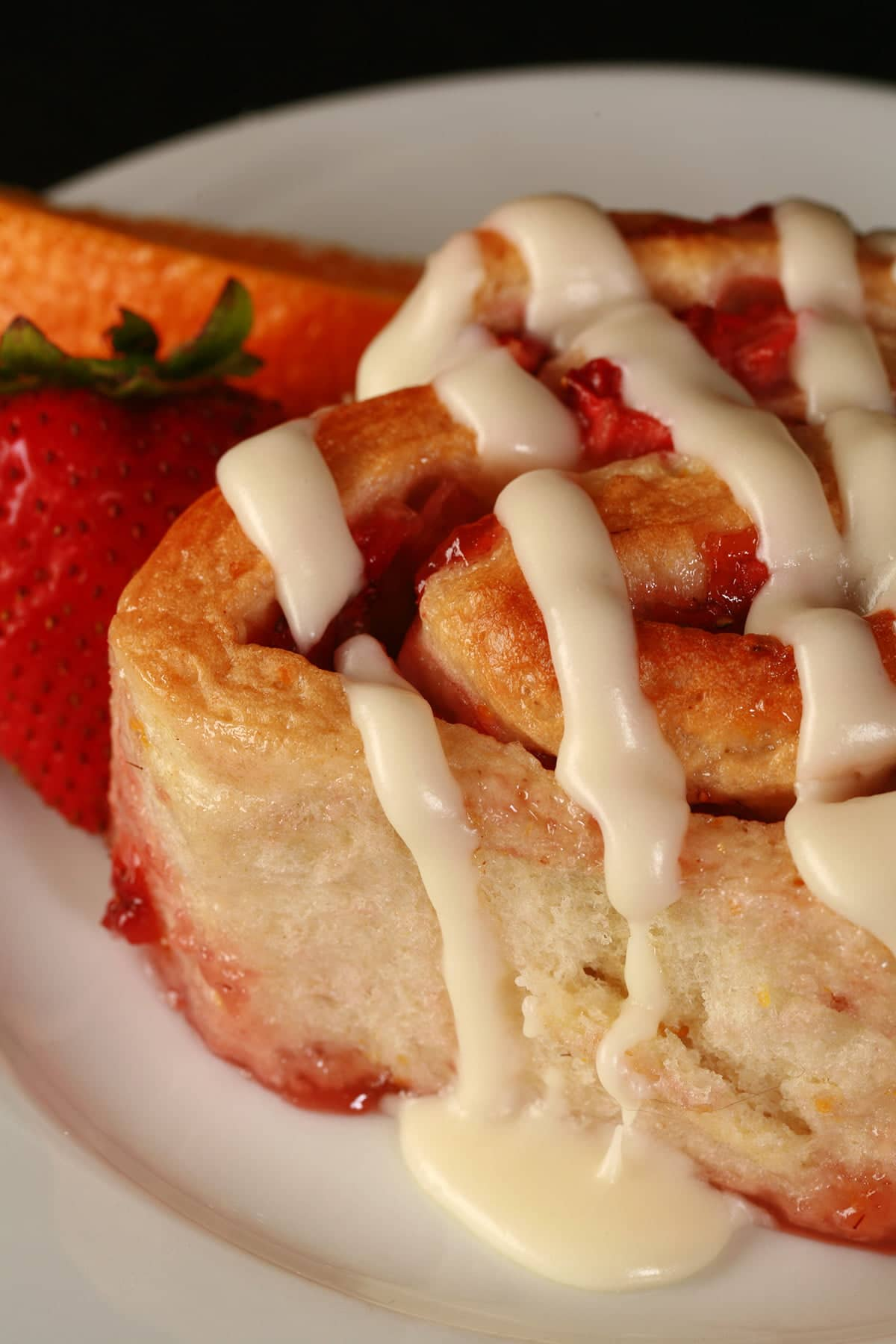 An orange strawberry roll on a white plate, with a fresh strawberry and an orange slice next to it