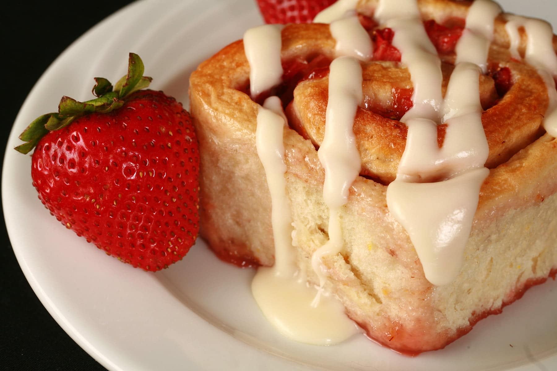 A orange strawberry roll on a white plate, with 2 fresh strawberries next to it