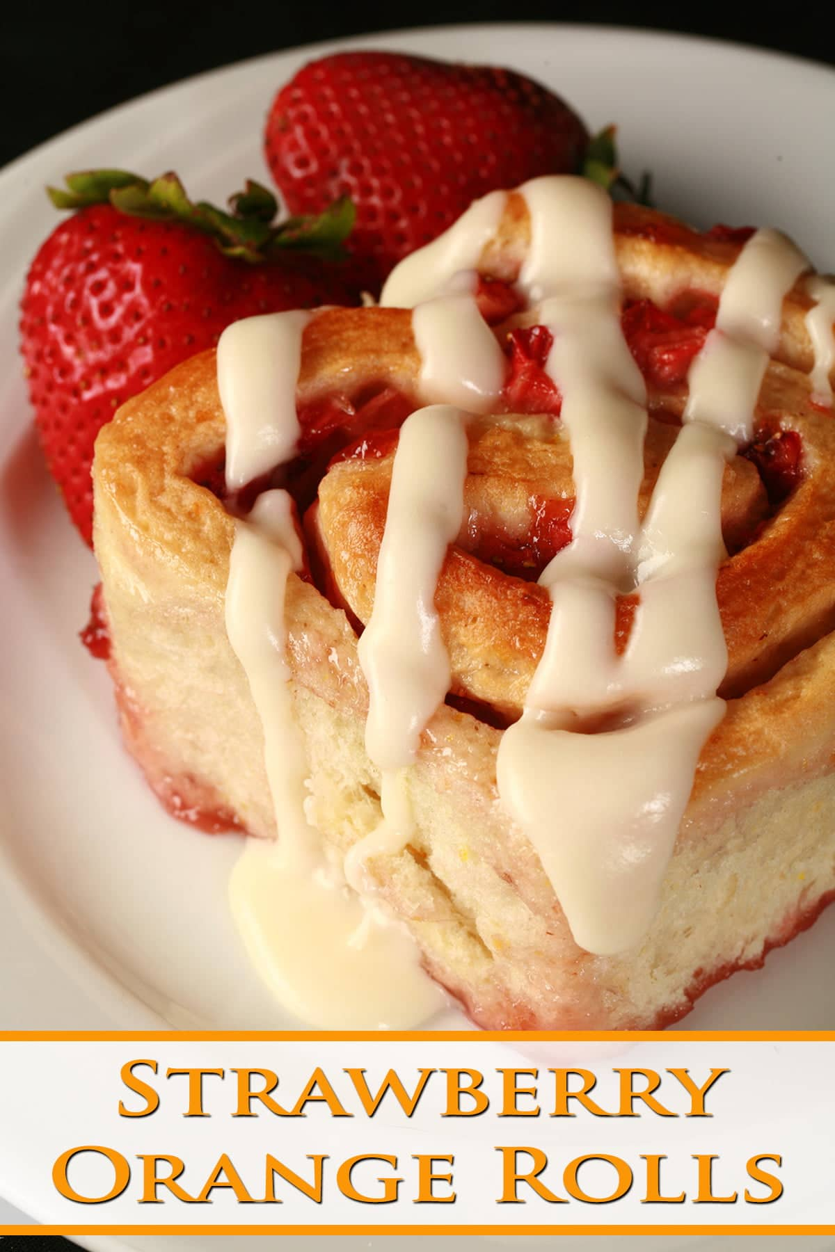 A strawberry orange roll on a white plate, with 2 fresh strawberries next to it