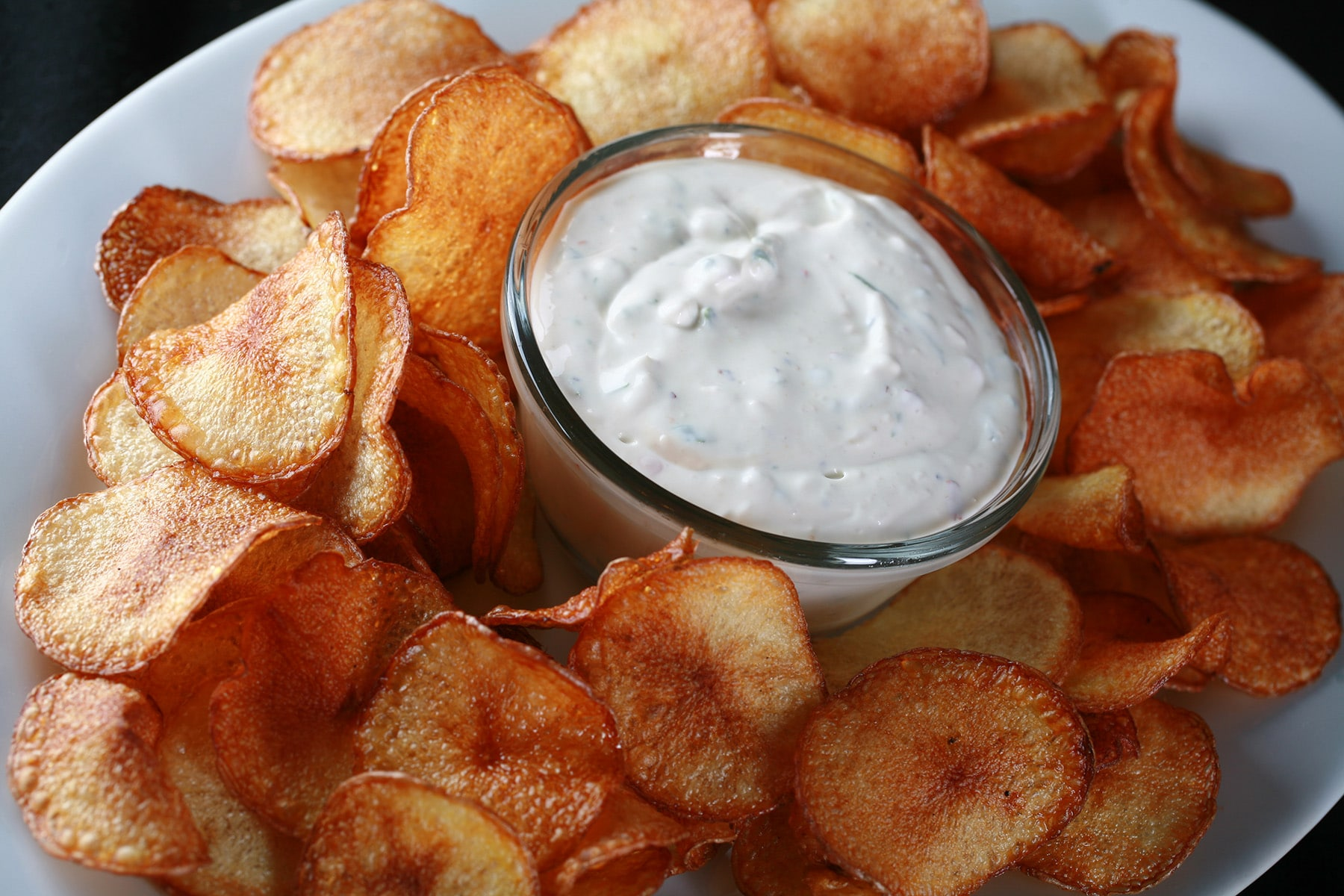 A large platter of cactus cut fries - spicy fried potato slices - with a bowl of cactus dip.