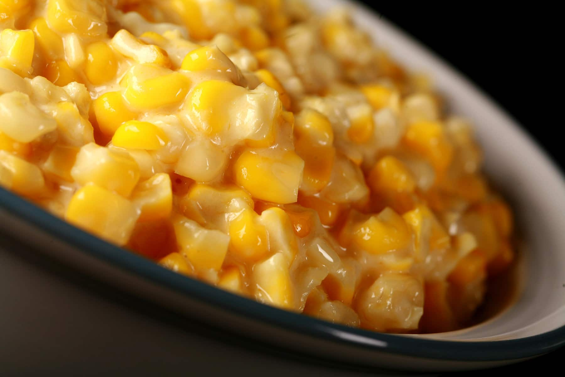 A large white bowl full of homemade creamed corn, against a black background.