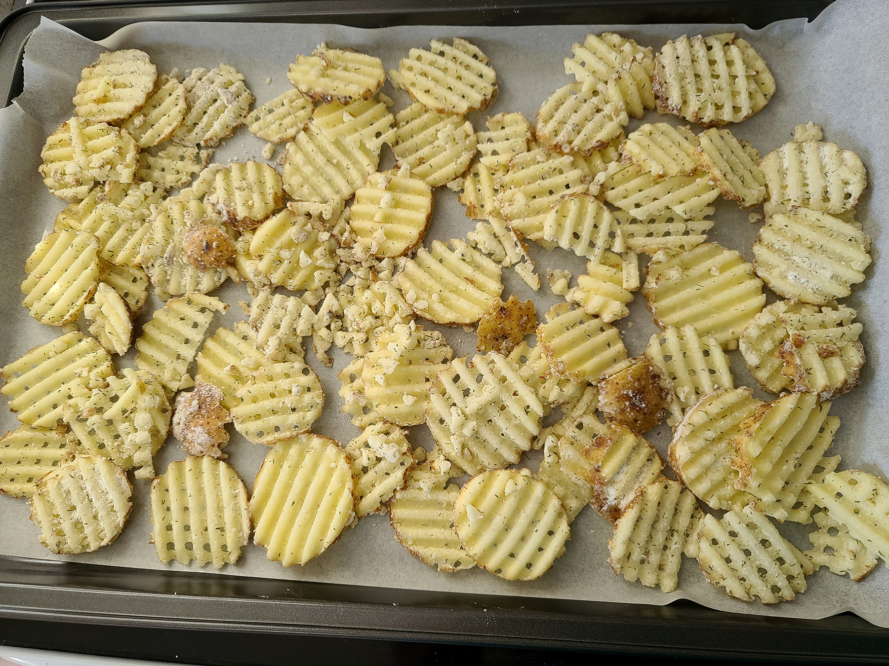 Coated homemade waffle cut fries on a baing sheet lined with parchment paper.