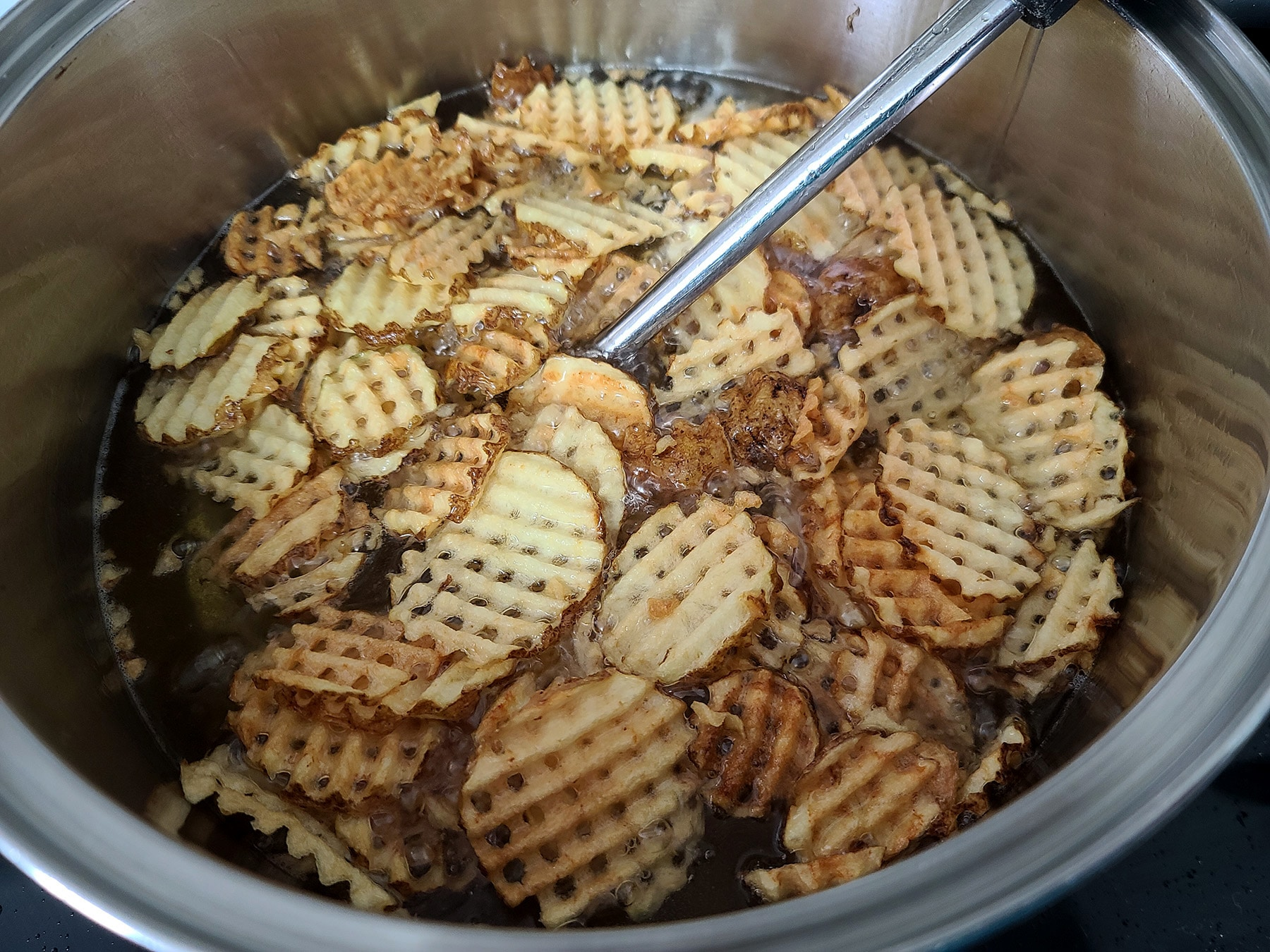A large pot of oil, deep frying waffle fries. The potatoes are golden brown this time.