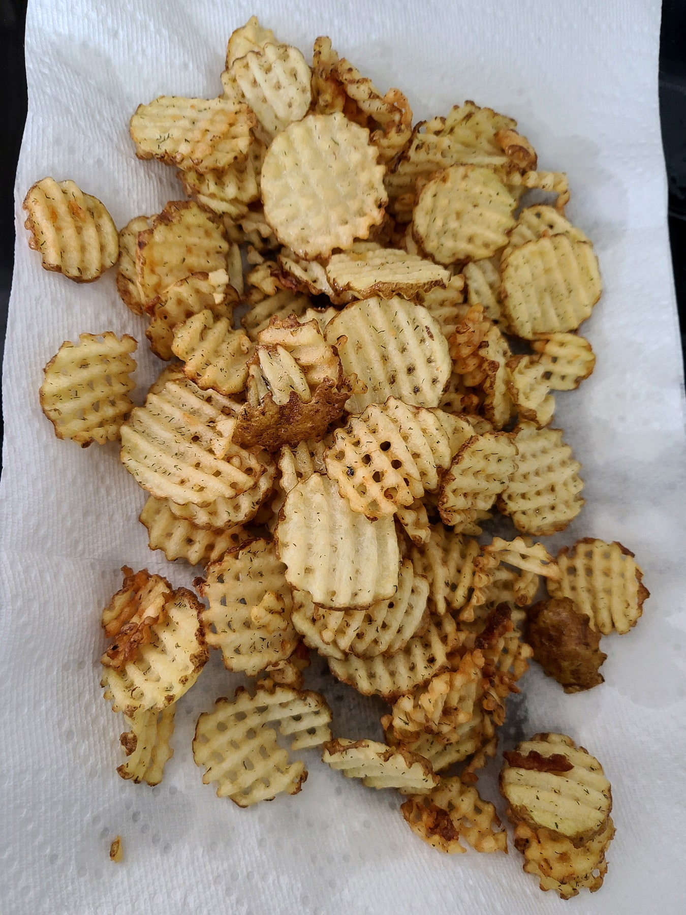 Golden brown waffle cut fries, on a baking sheet lined with paper towels.