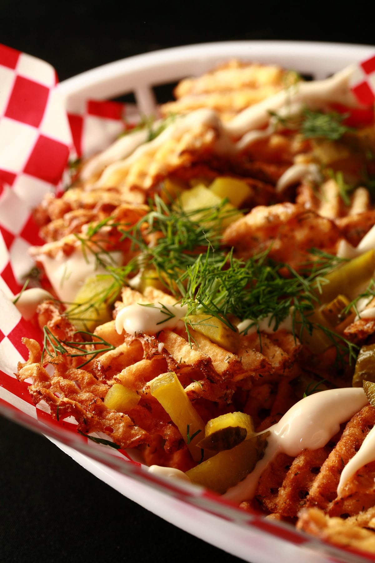 Dill Pickle waffle fries, in a white basket lined with red and white checkered paper. The fries are drizzled with roasted garlic aioi and topped with chopped dill and chopped pickles.