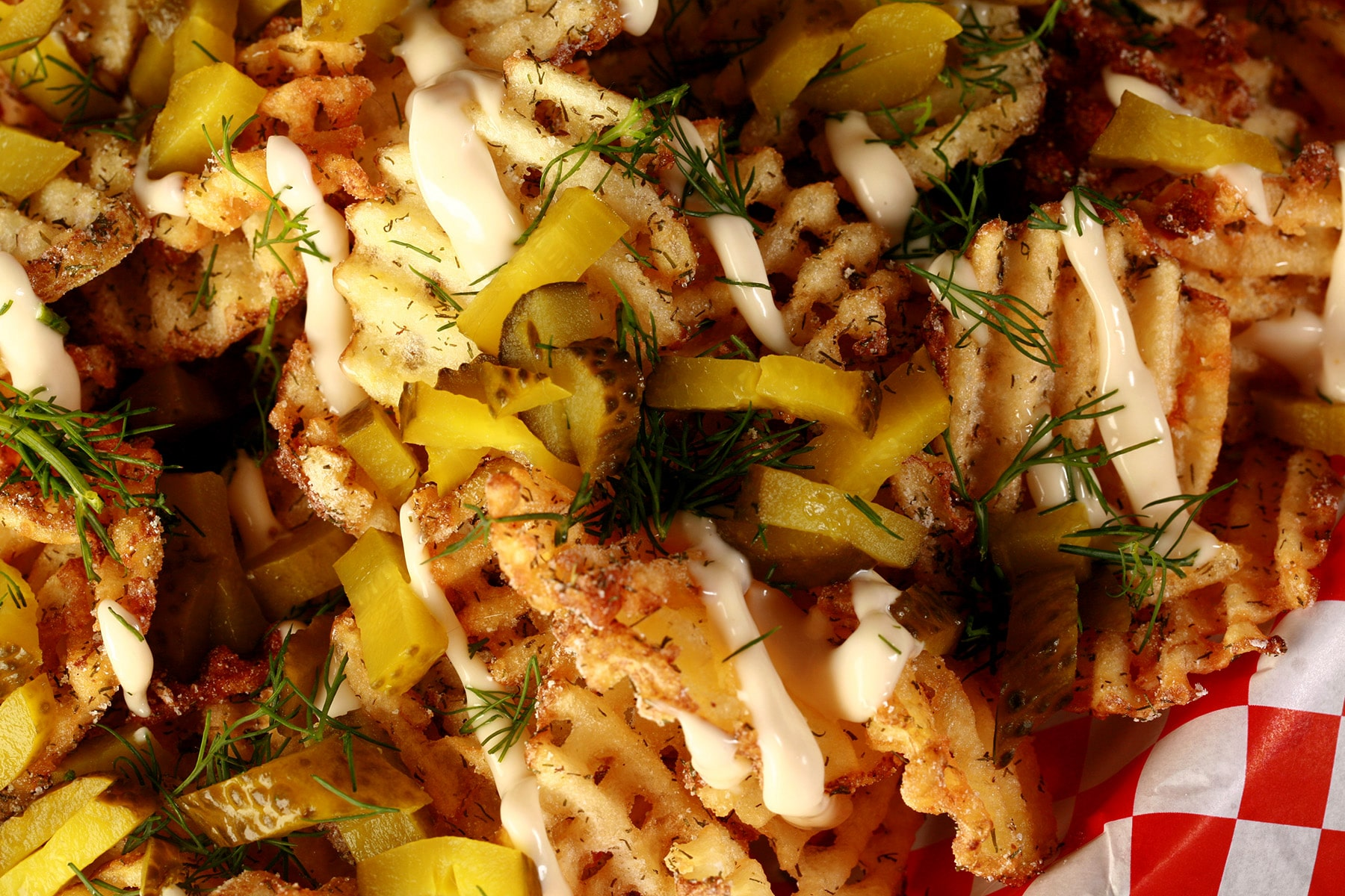 Waffle cut fries, in a white basket lined with red and white checkered paper. The fries are drizzled with roasted garlic aioi and topped with chopped dill and chopped pickles.