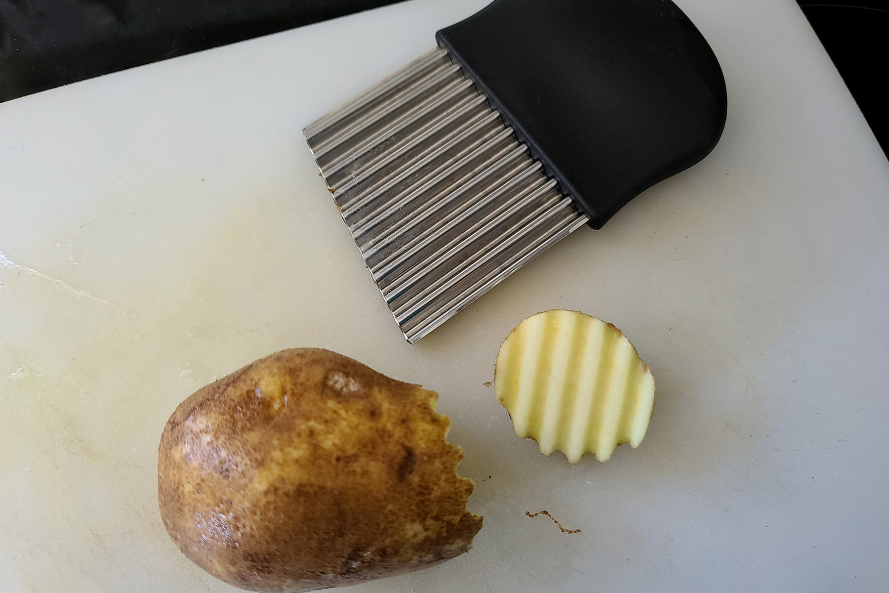 A potato and a crinkle cut knife on a cutting board, along with the crinkle cut end of the potato that has been cut off.