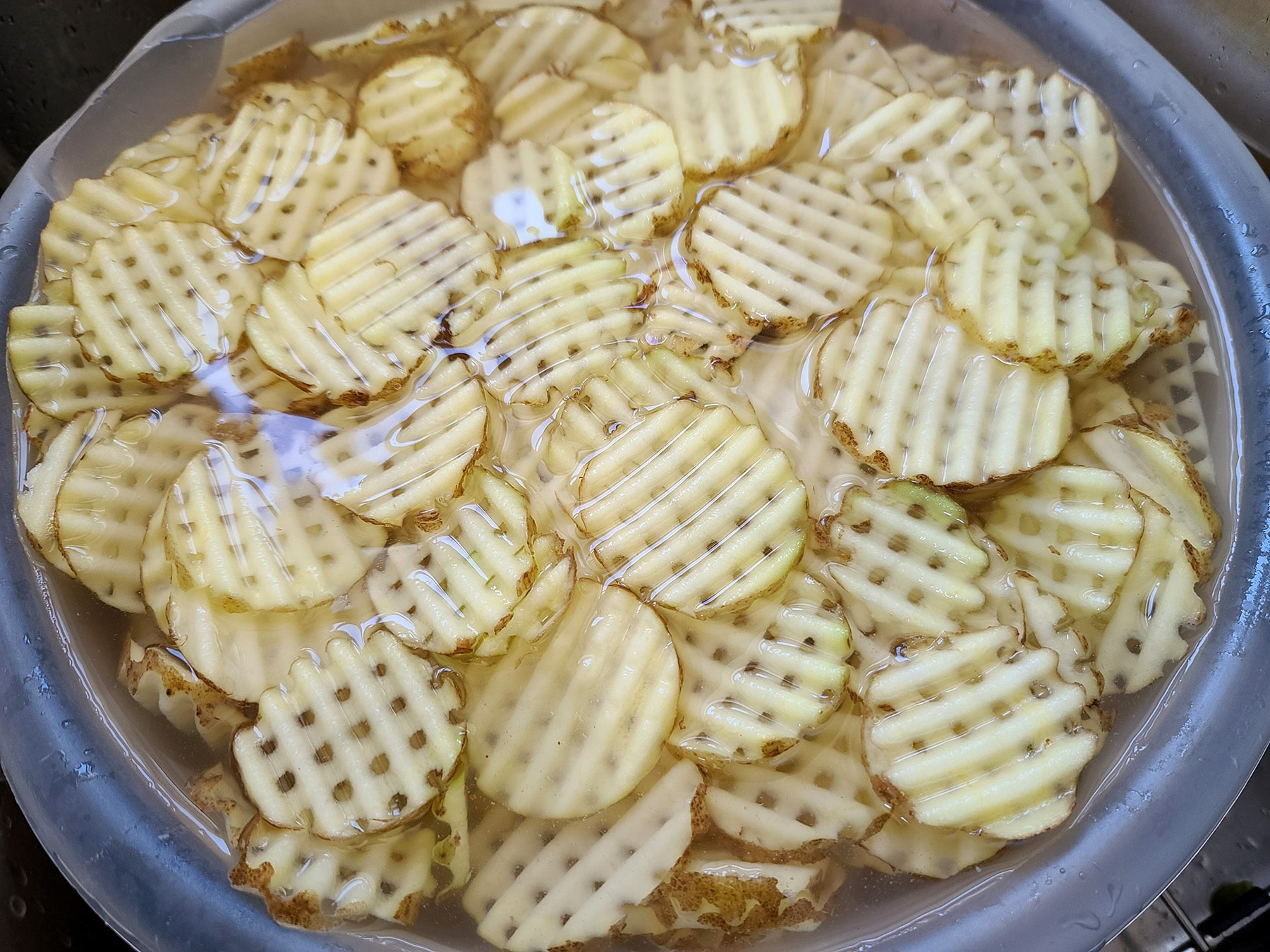 A large white bowl of waffle cut potatoes soaking in water.