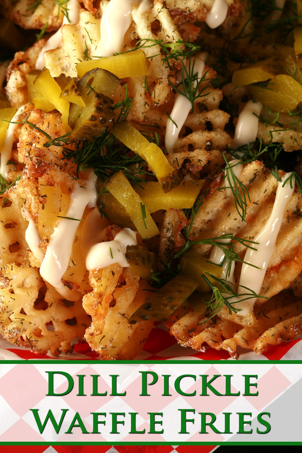 Waffle cut fries, in a white basket lined with red and white checkered paper. The fries are drizzled with roasted garlic aioi and topped with chopped dill and chopped pickles. Green Text overlay says Dill Pickle Waffle Fries.