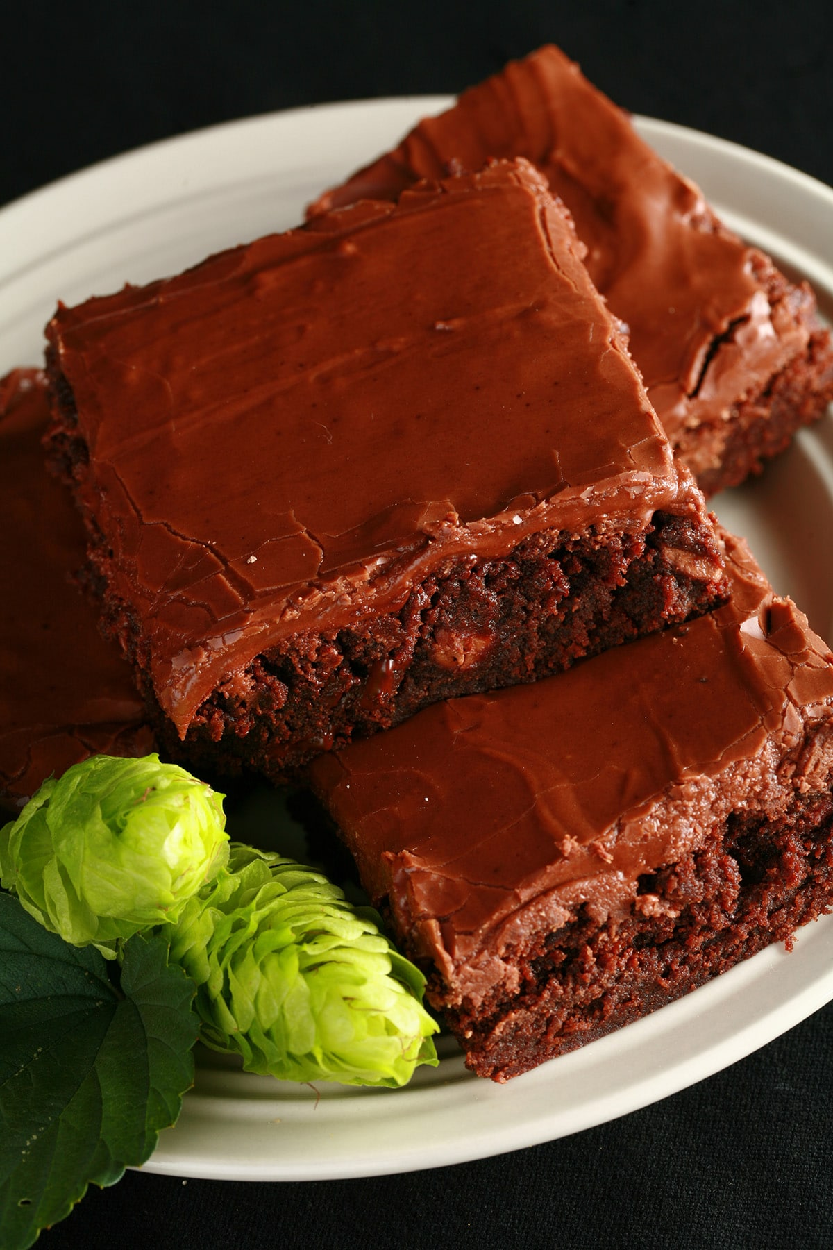 A small stack of dark, , rich, gooey looking chocolate hop brownies. The small white plate is garnished with 2 fresh hop flowers.