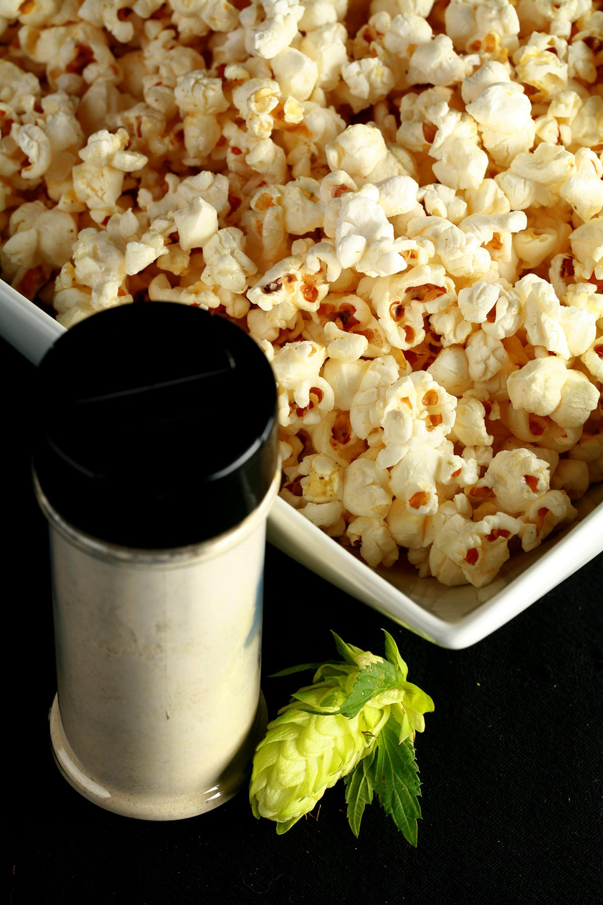 A large rectangular bowl holds hop-seasoned popcorn - hopcorn! There is a small canister of the popcorn seasoning, and a fresh hop flower next to the bowl.