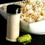 A large rectangular bowl holds hopped popcorn - hopcorn! There is a small canister of the popcorn seasoning, and a fresh hop flower next to the bowl.
