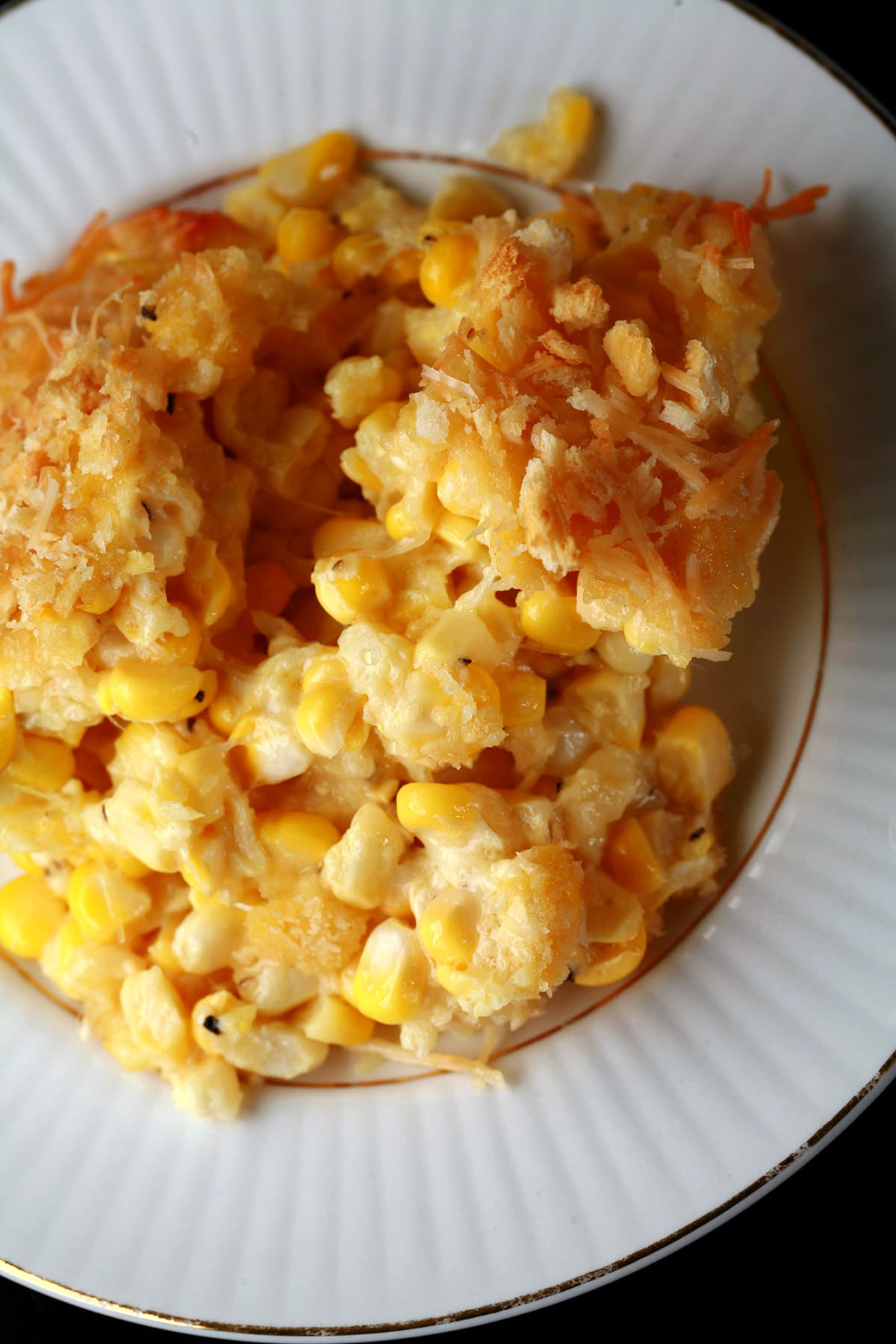A serving of scalloped corn - fresh sweet corn, cheese, crackers, and more - on a small white plate.