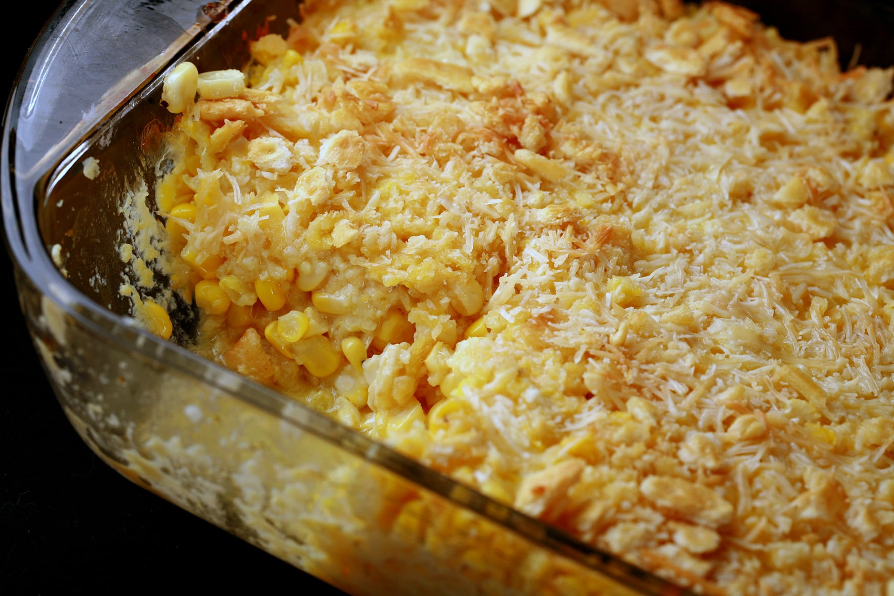 A pan of baked scalloped sweet corn. It has a golden brown crust of cheese and crackers on top.
