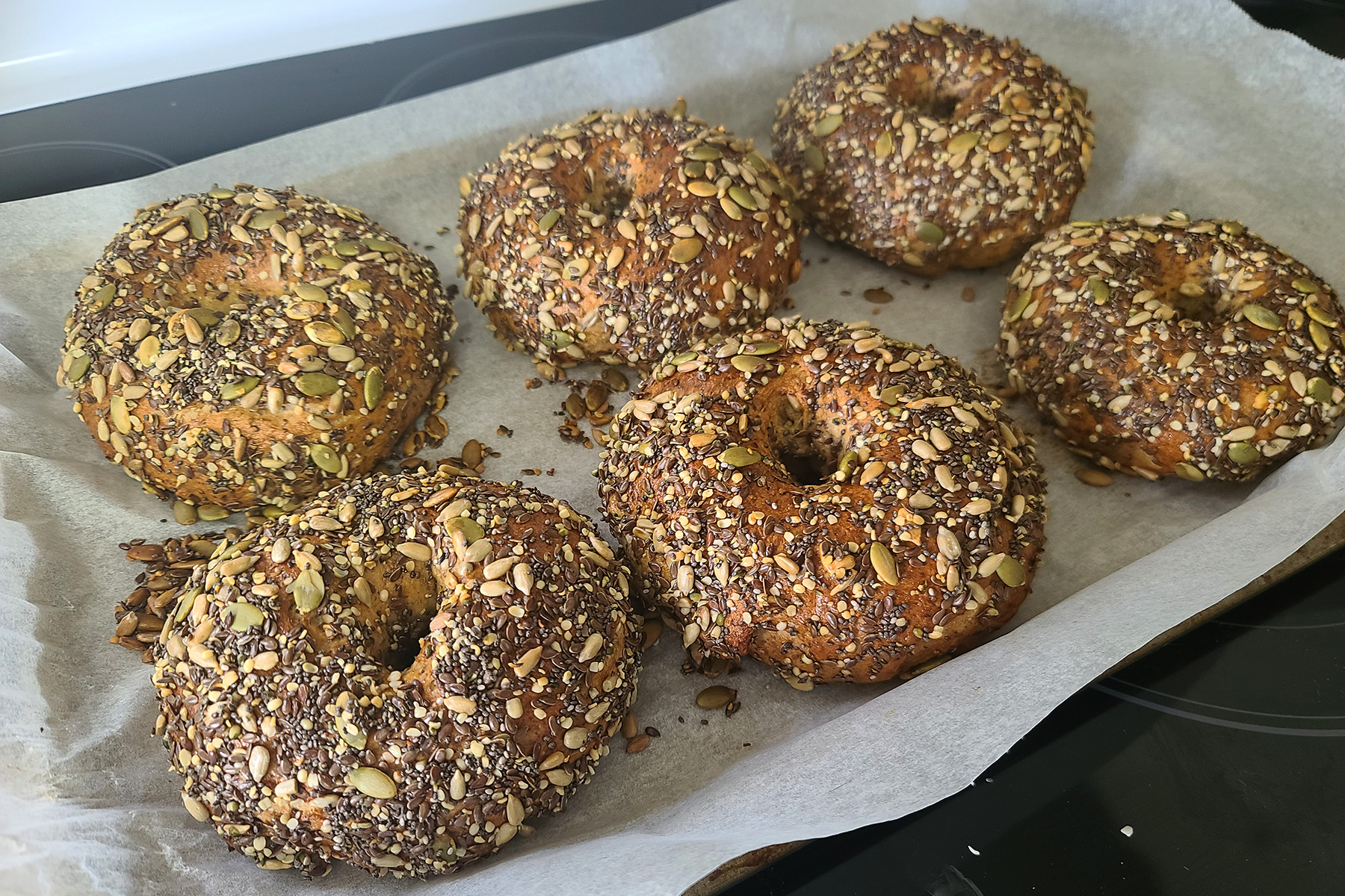 6 golden brown seeded whole wheat flax bagels arranged on a parchment lined baking sheet, fresh from the oven.