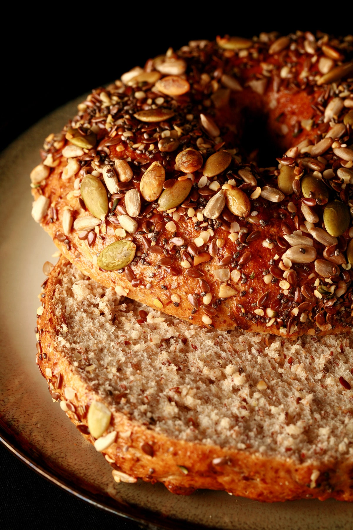 A whole wheat and flax bagel, sliced and served on a small plate. The top side of the bagel is covered in a mix of seeds - pumpkin, sunflower, sesame, chia, and poppy.