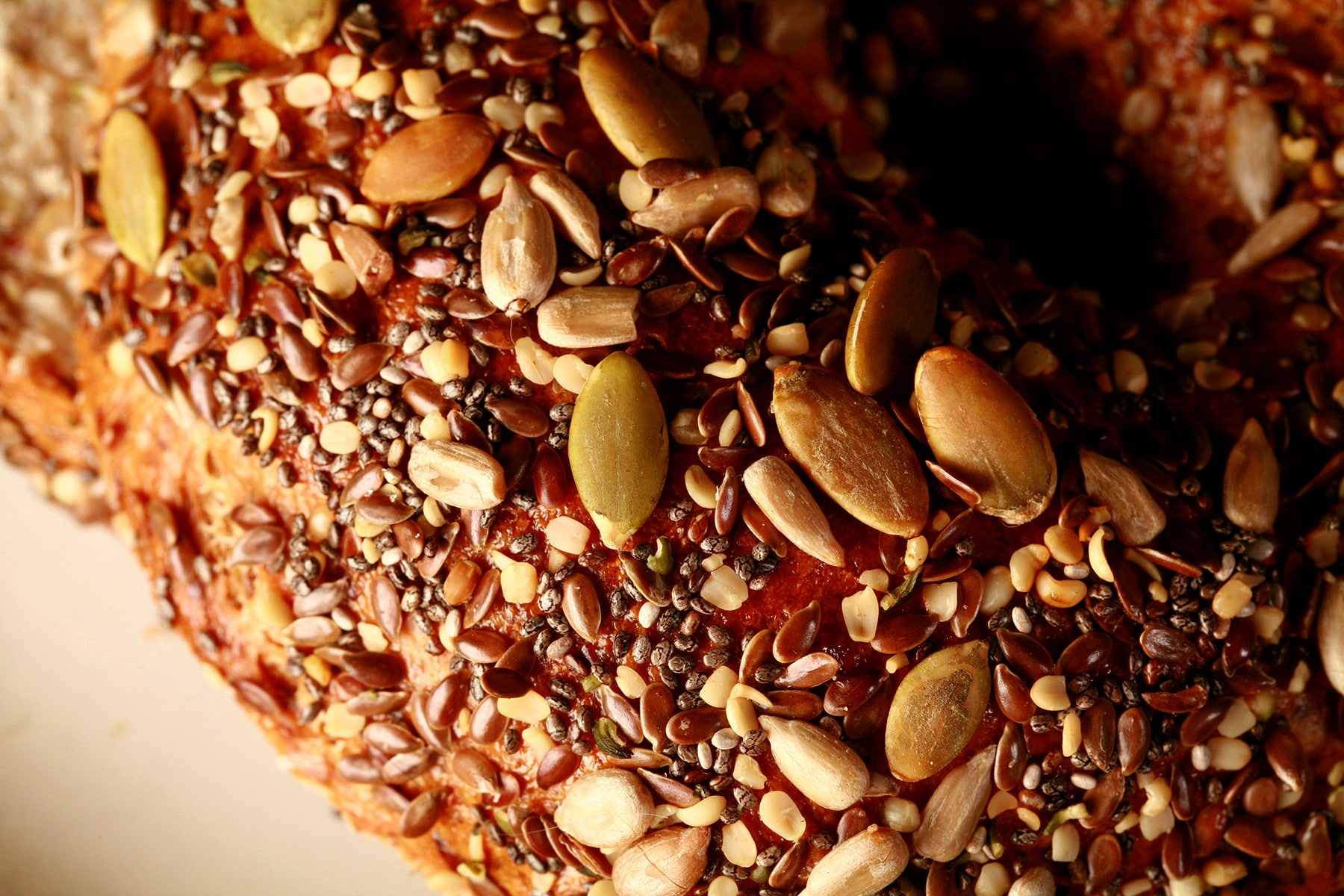 A close up view of the top of a seeded whole wheat flax bagel. The top is covered in a mix of seeds - pumpkin, sunflower, flax, sesame, chia, and poppy.