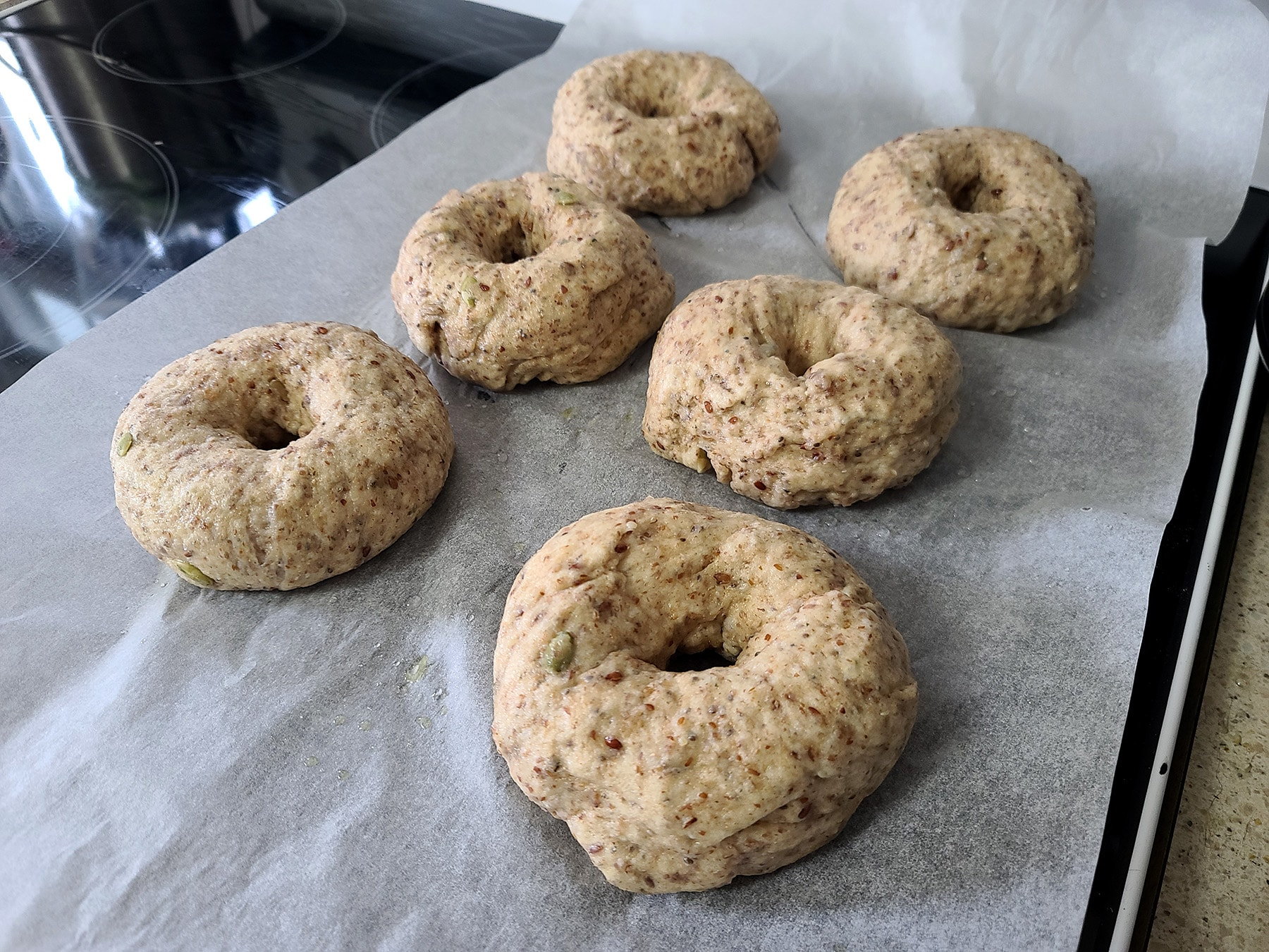 6 boiled seeded whole wheat flax bagels resting on a parchment lined baking sheet.