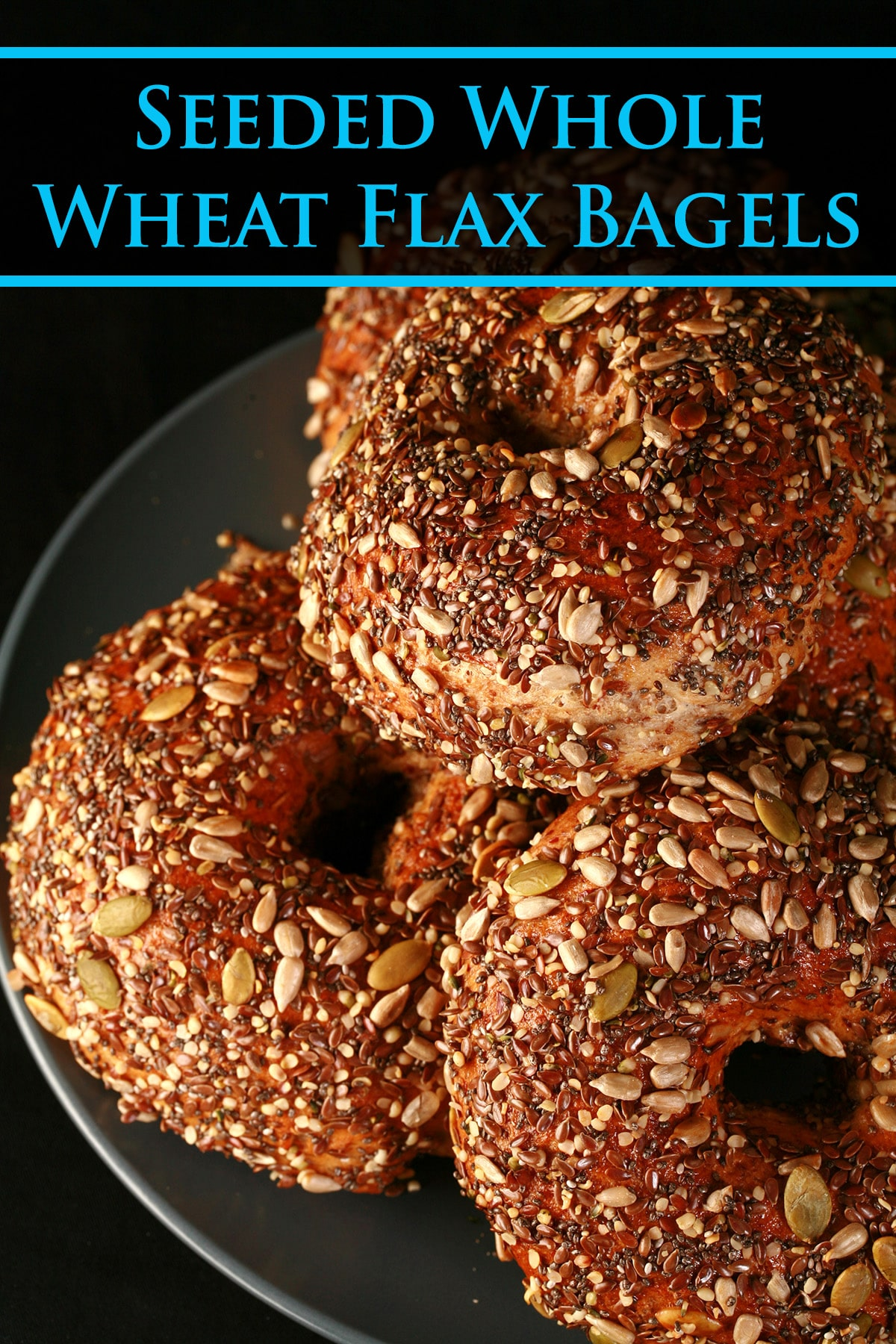 A plate stacked with a pile of whole wheat and flax bagels. The top side of each bagel is covered in a mix of seeds - pumpkin, sunflower, flax, sesame, chia, and poppy.