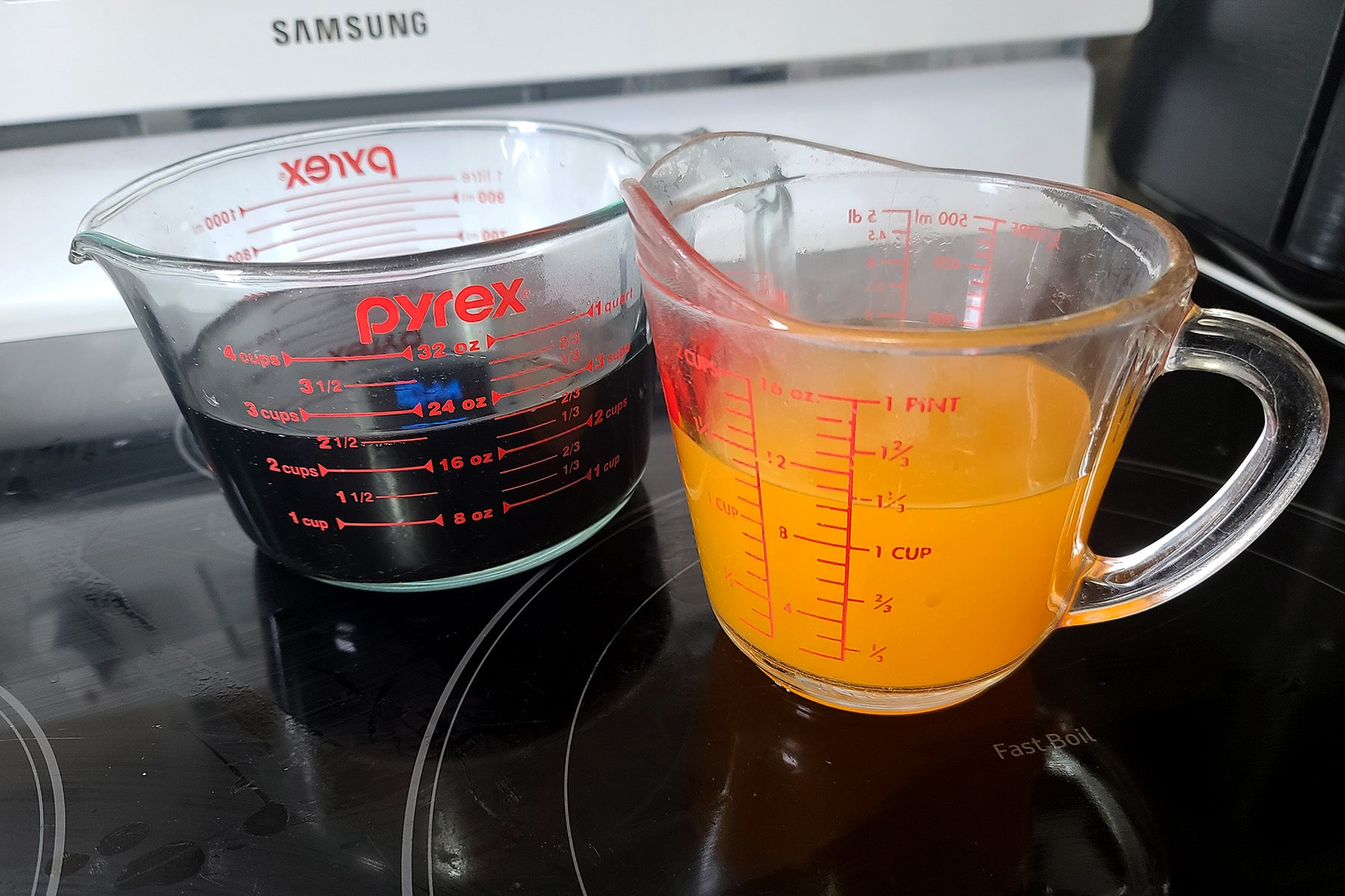 Two glass measuring cups - one with root beer mixture, the other with orange soda mixture - sitting next to each other, steaming.