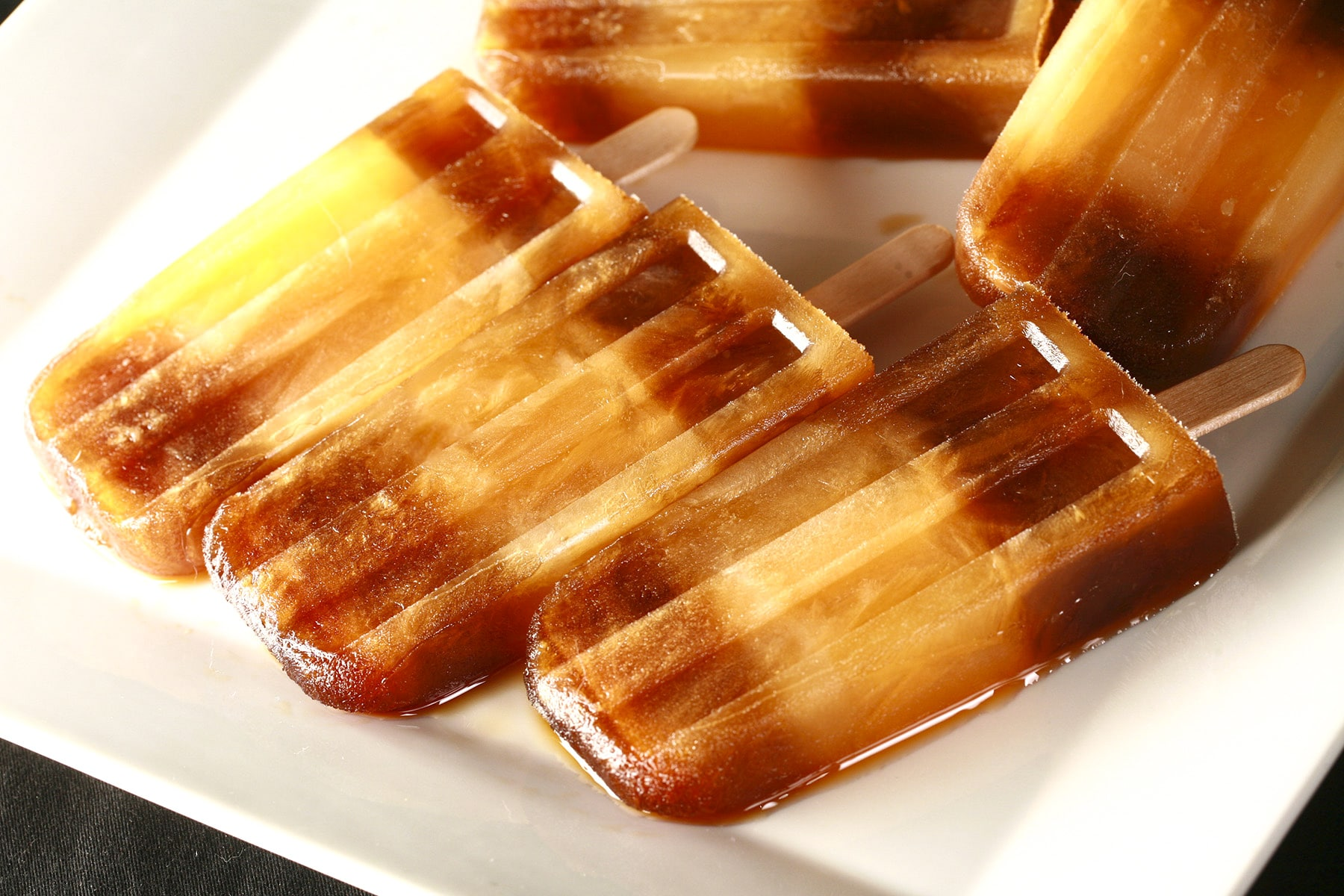"""Several frozen root beer popsicles with a stripe of orange soda in the middle - are laid out on a white plate. These are a homemade version of """"Space Shuttle"""" popsicles, a discontinued Dickie Dee item."""