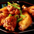 A small black plate with a pile of Spicy Ginger Wings piled on it, topped with slices of green onion.