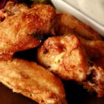 A close up view of a plate of tangerine-thyme dry rub seasoned wings.