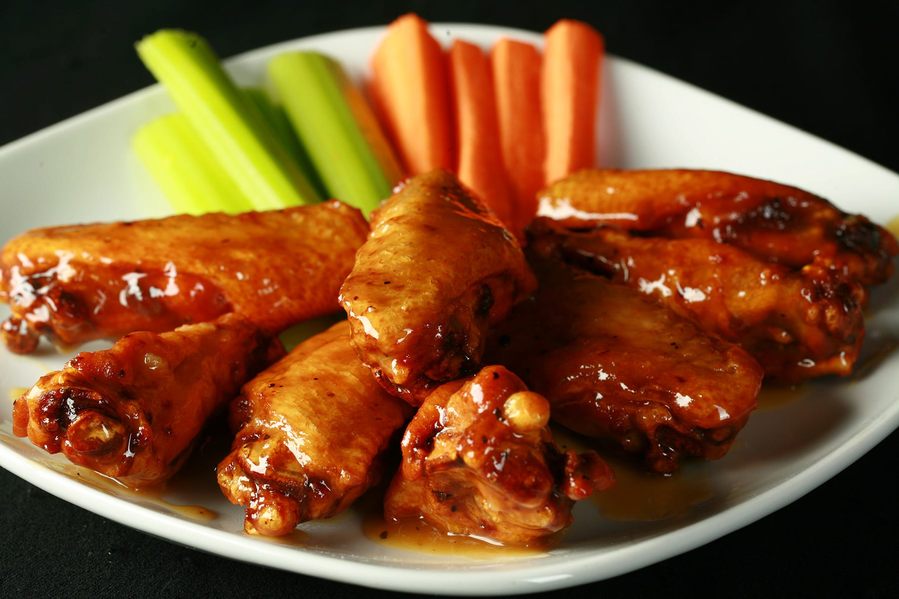 A small white plate with a pile of Whisky Honey Mustard Wings piled on it, celery and carrot sticks on the side.