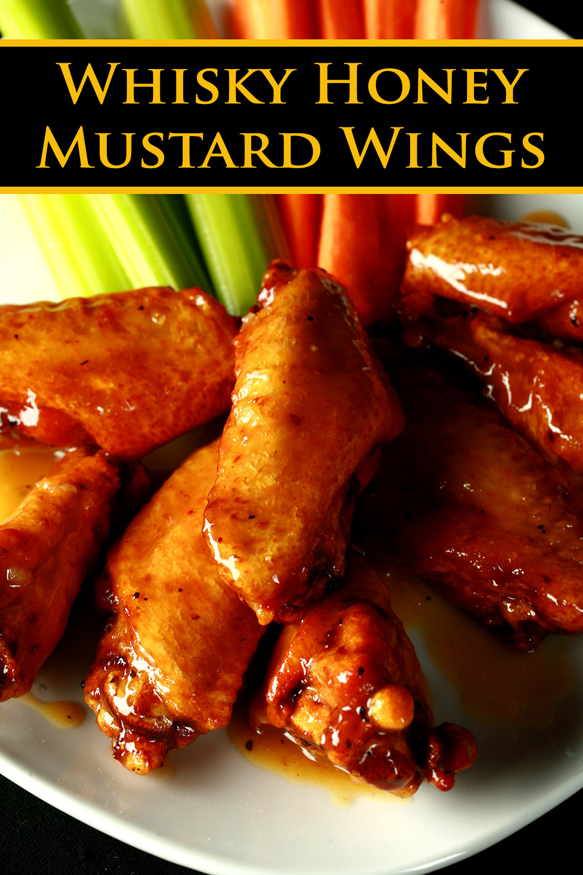 A small white plate with a pile of Whisky Honey Mustard Glazed Wings piled on it, celery and carrot sticks on the side.