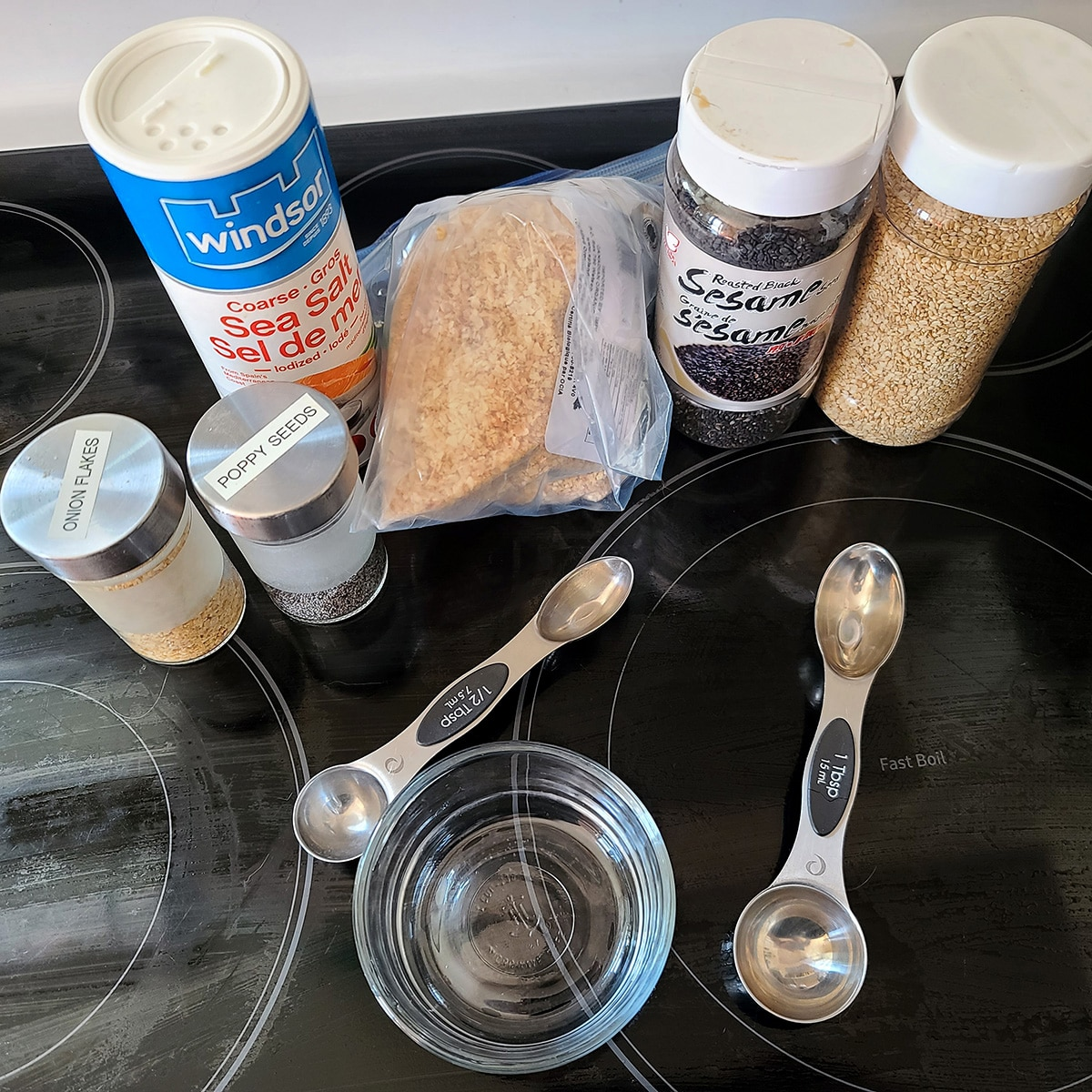 All of the ingredients for making everything bagel seasoning, laid out on a stovetop.
