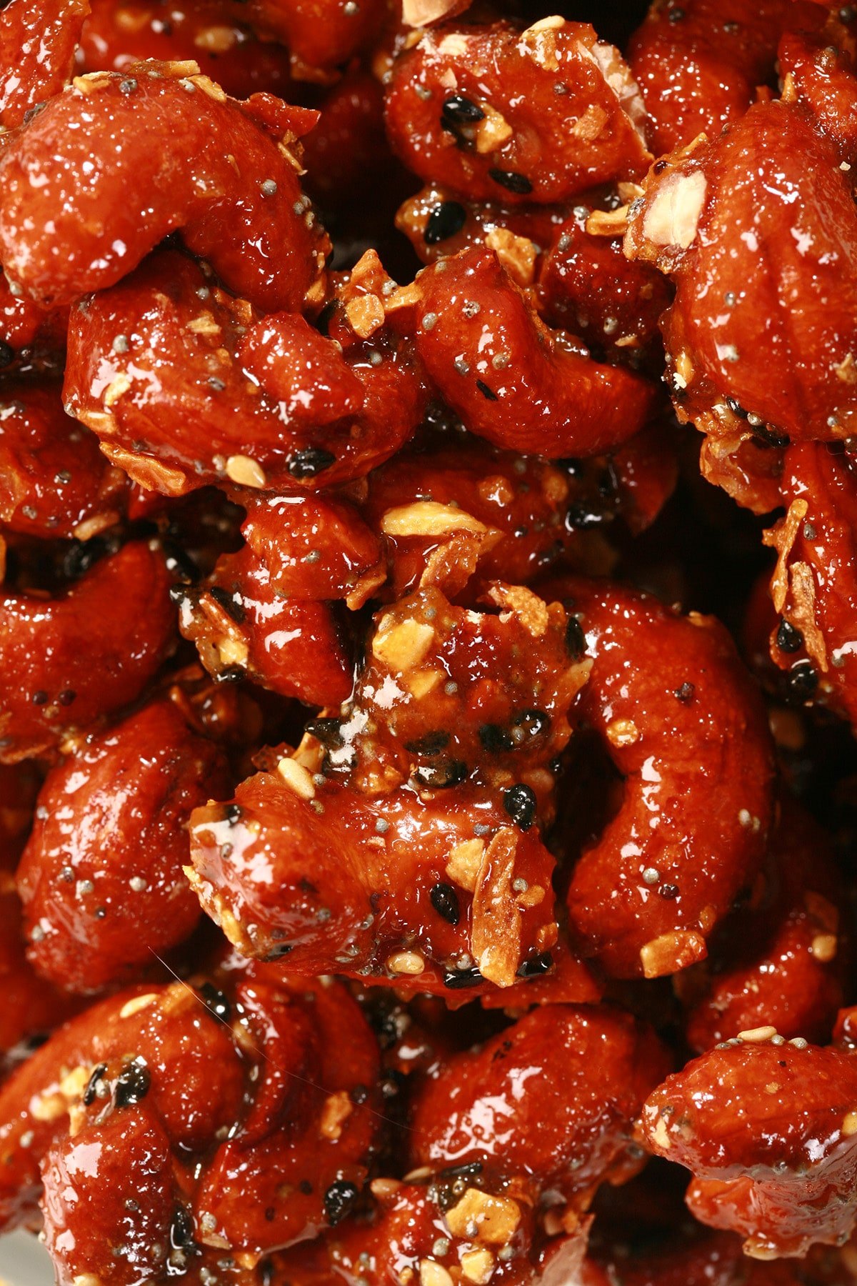 A close up view of Honey Glazed Everything Cashews in a glass bowl. They are crusted with a deep reddish brown caramel, and coated with bagel seasoning.