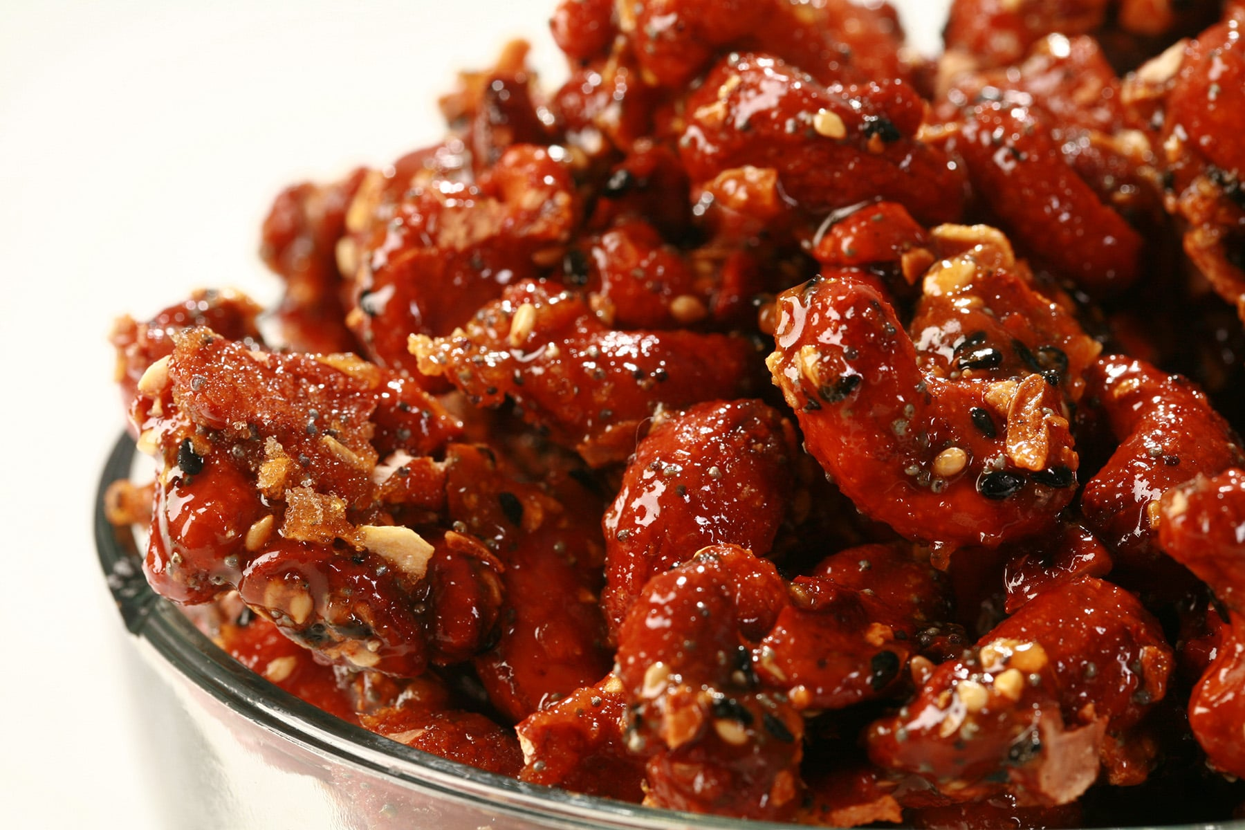 A close up view of Everything Honey Glazed Cashews in a glass bowl. They are crusted with a deep reddish brown caramel, and coated with bagel seasoning.