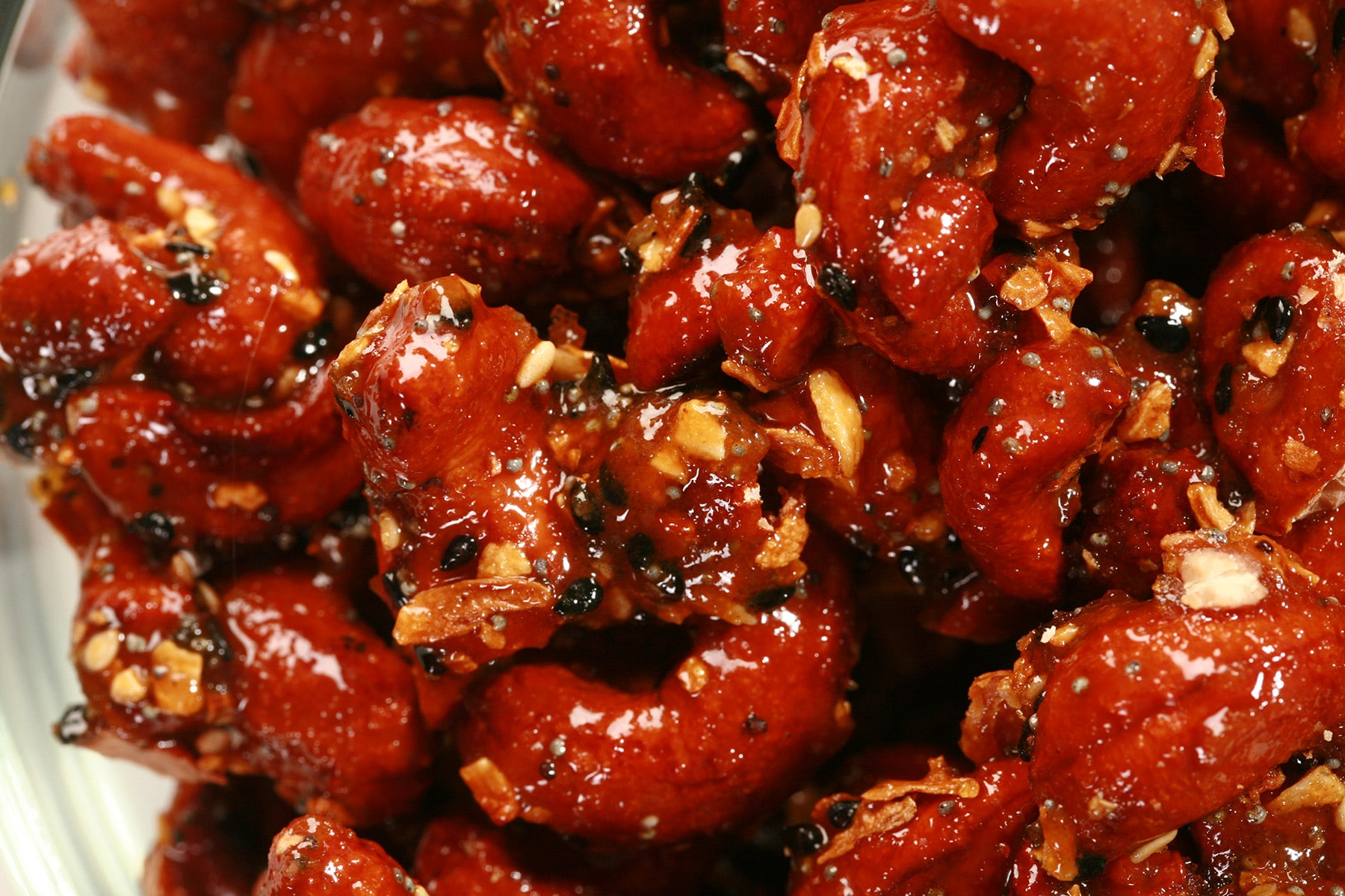 A close up view of Honey Glazed Cashews in a glass bowl. They are crusted with a deep reddish brown caramel, and coated with everything bagel seasoning.