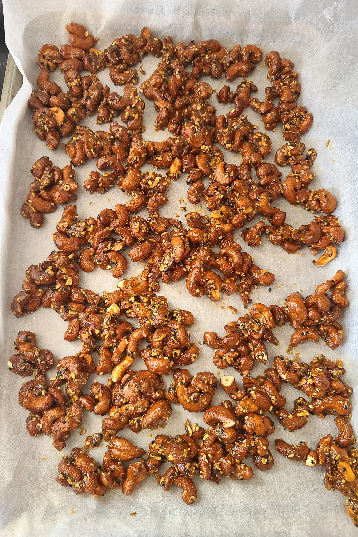 Everything Seasoned Honey Glazed cashews, spread out on a parchment lined pan.