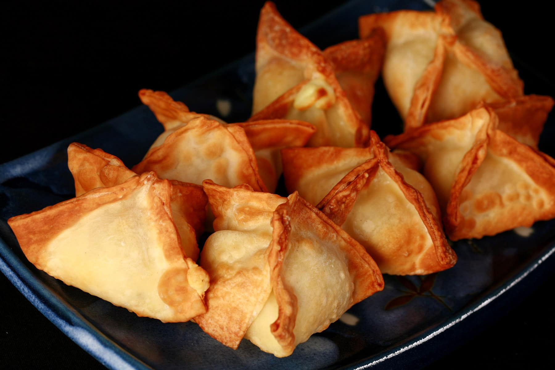 A small, blue, rectangular dish with pyramid shaped air fryer cream cheese wontons on it., rectangular dish with pyramid shaped air fryer cream cheese wontons on it.
