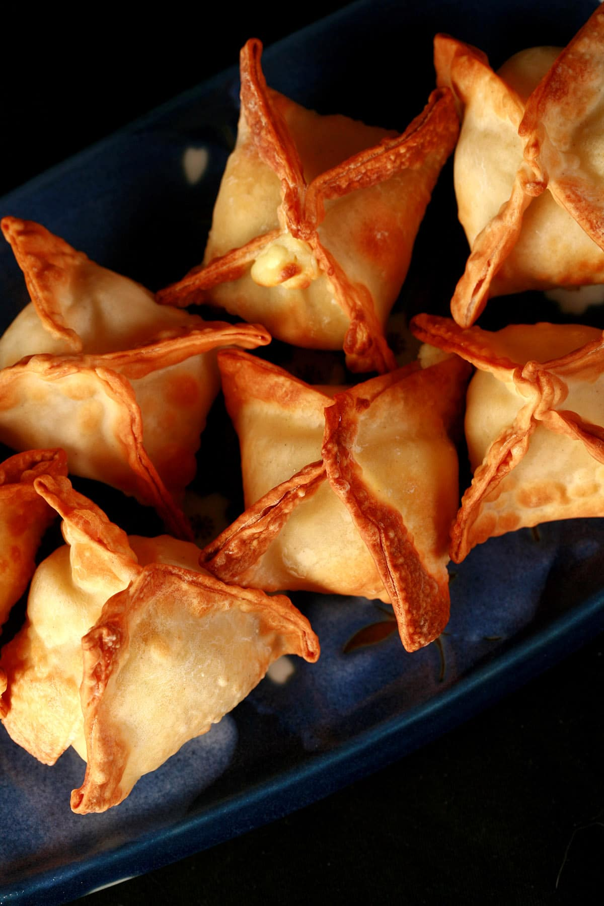 A small, blue, rectangular dish with pyramid shaped air fried cream cheese wontons on it.