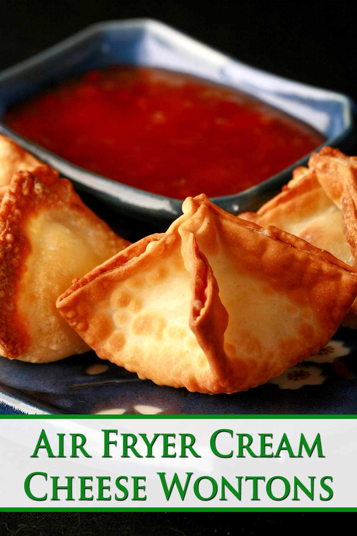 A small, blue, rectangular dish with pyramid shaped air fryer cream cheese wontons on it.